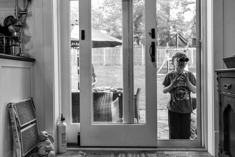 boy looks in the window with binoculars
