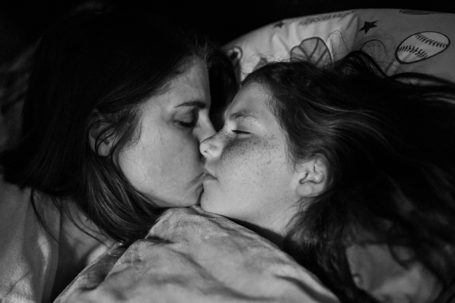 mom kisses her daughter goodnight