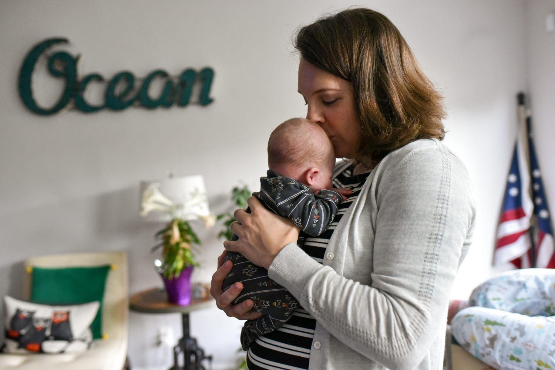 mom snuggles newborn son in alexandria