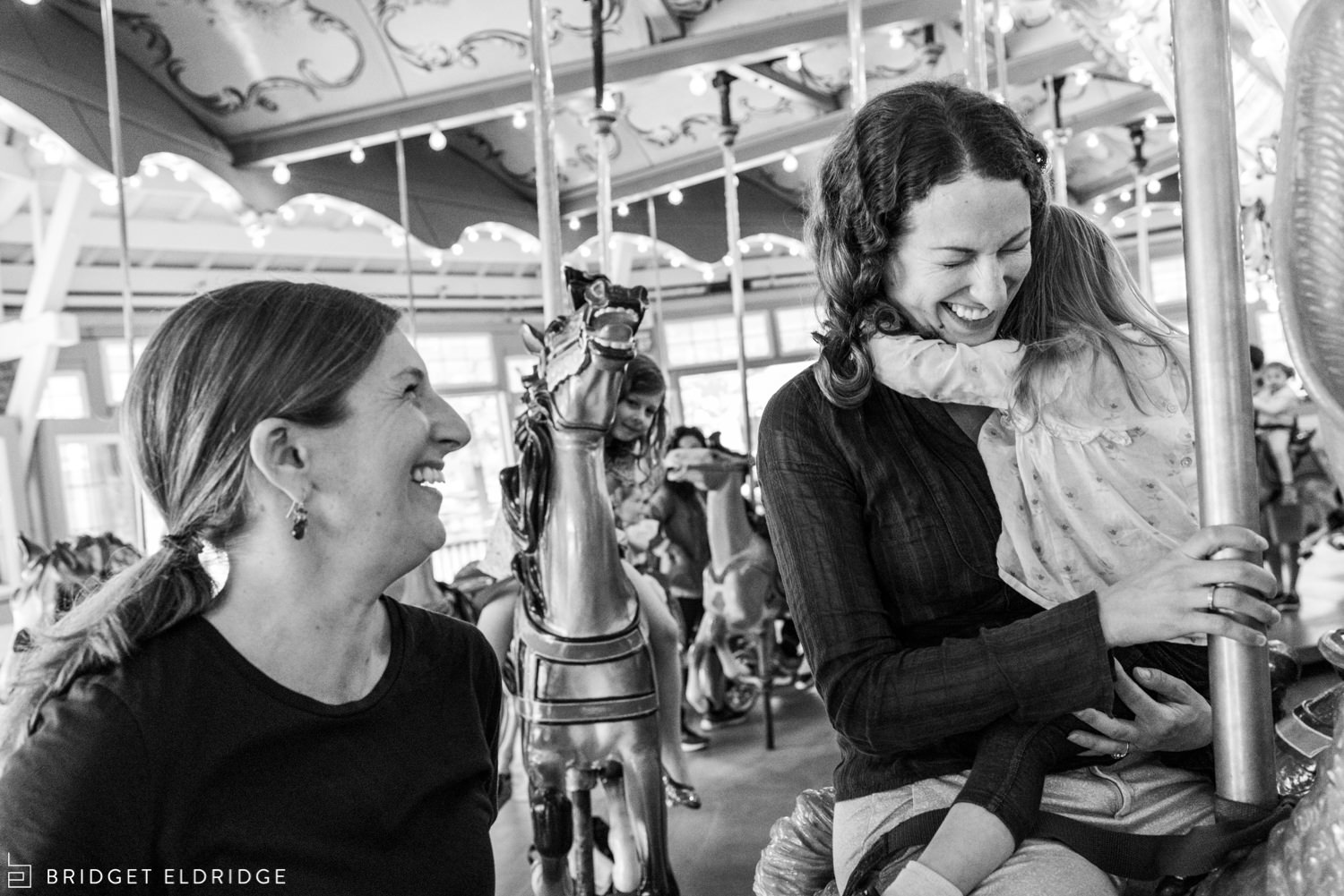 sisters laugh on the carousel at glen echo park