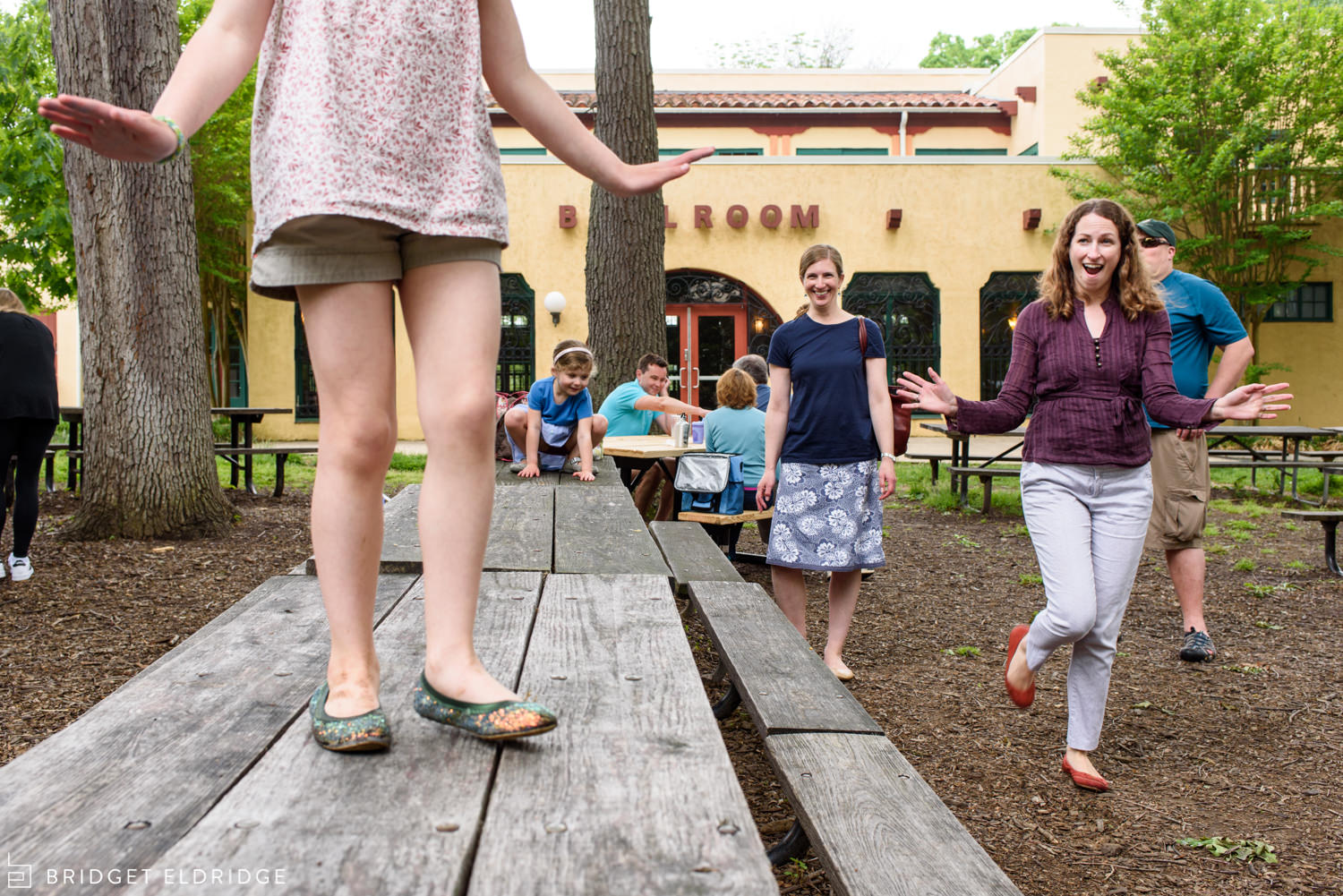 aunt watches her niece dance on a picnic table