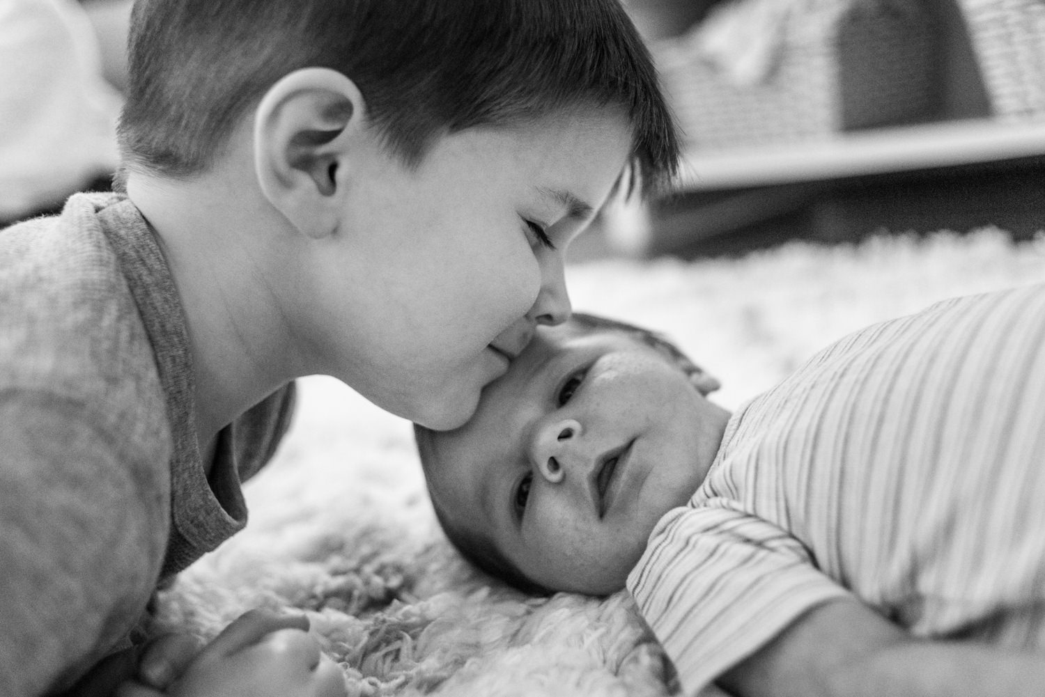 brother gives newborn a kiss