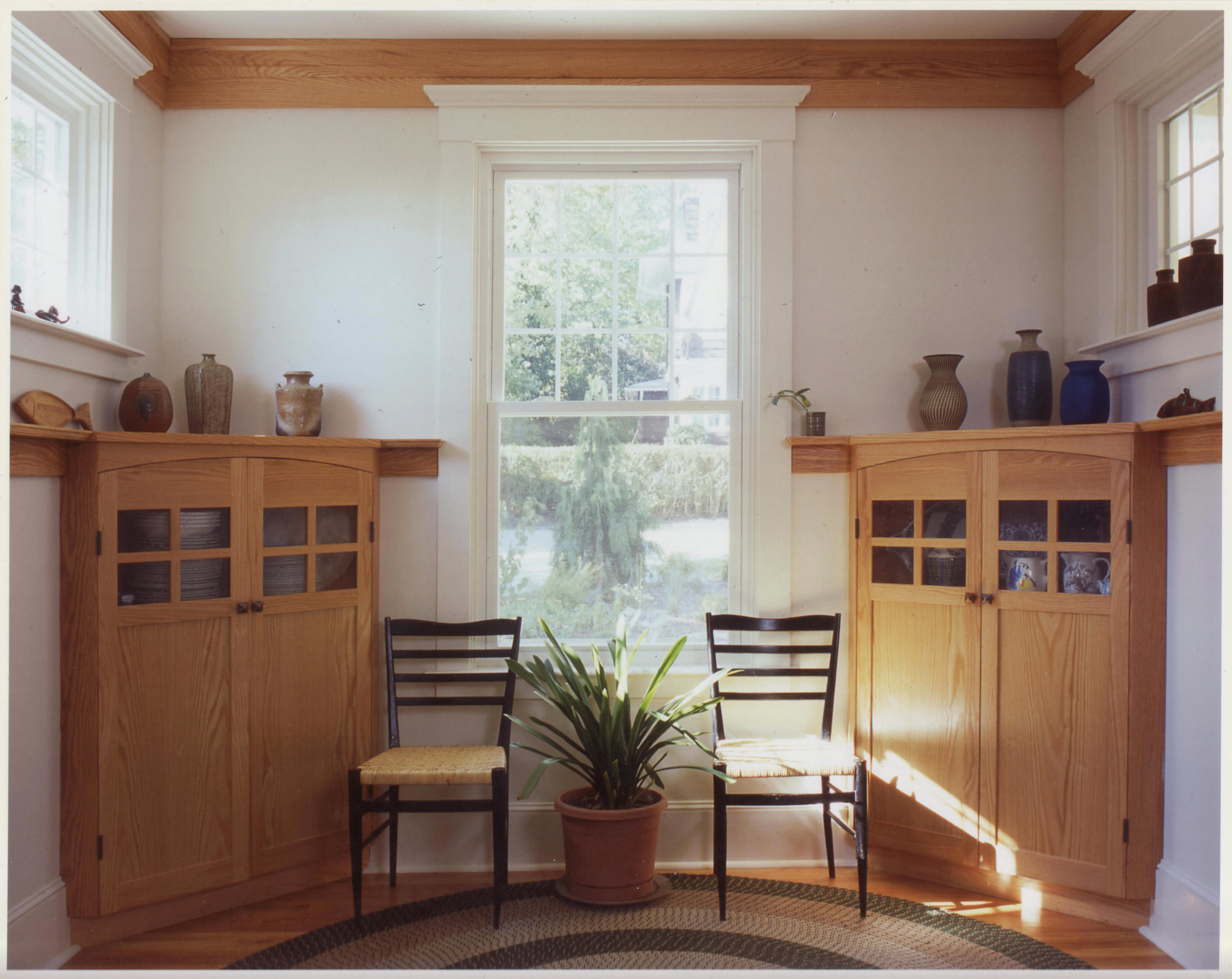 Custom designed corner cabinets embrace the new breakfast alcove, created by enclosing an existing exterior porch.