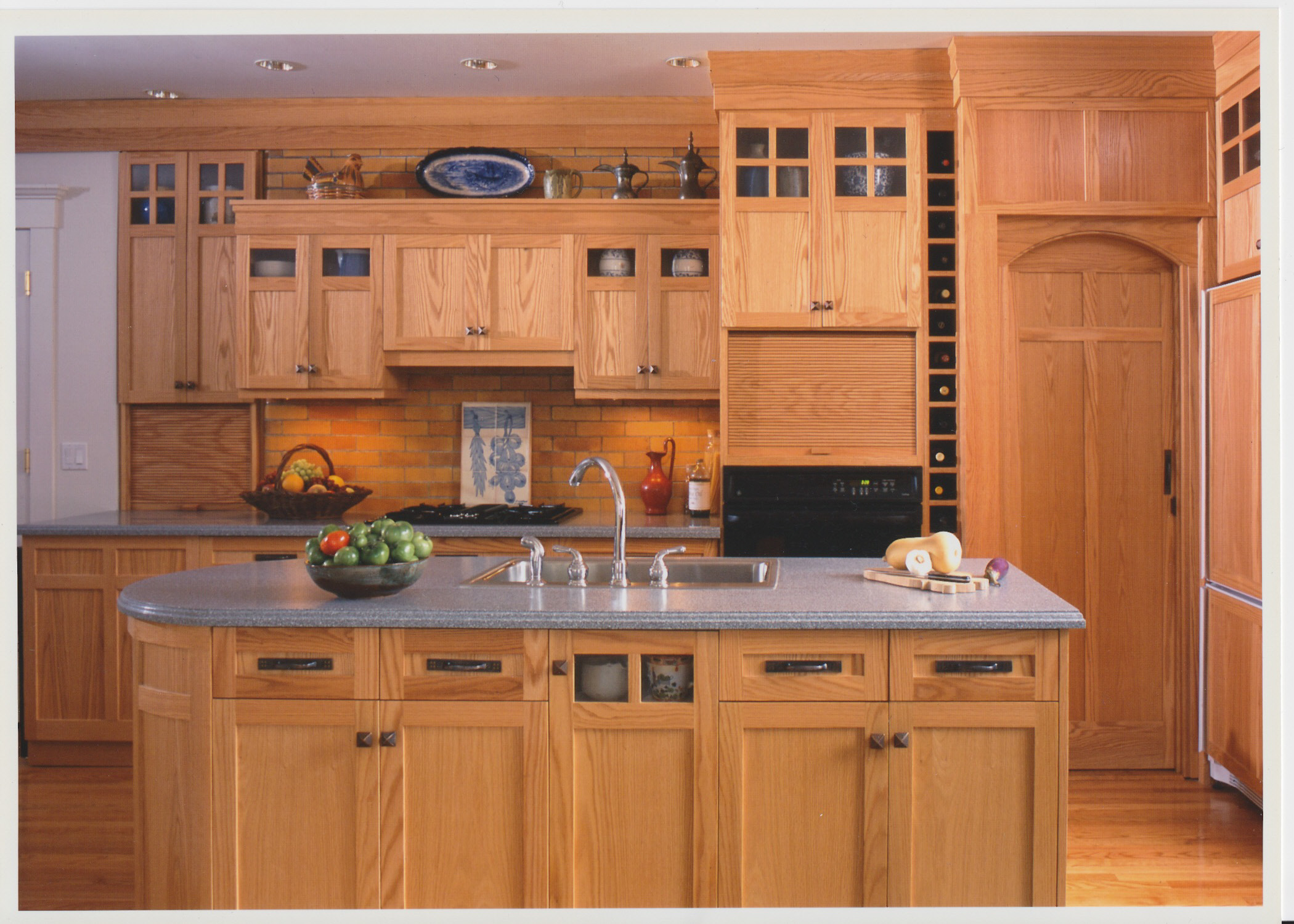 The cabinetry design blends with the style of the house, a large Arts  and Crafts style home on the shores of Long Island Sound. The brick  backsplash is actually the backside of the fireplace. The arched door at  the right opens into a pantry built under the stairs to the second  floor.