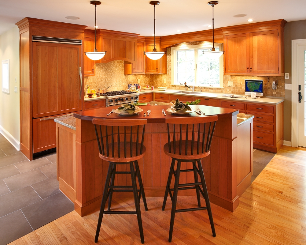 The working portion of the Kitchen is anchored in the corner, while the  breakfast bar provides a wonderful opportunity to converse with the  cook. Cabinetry by Kitchens by Gedney, of Madison, CT