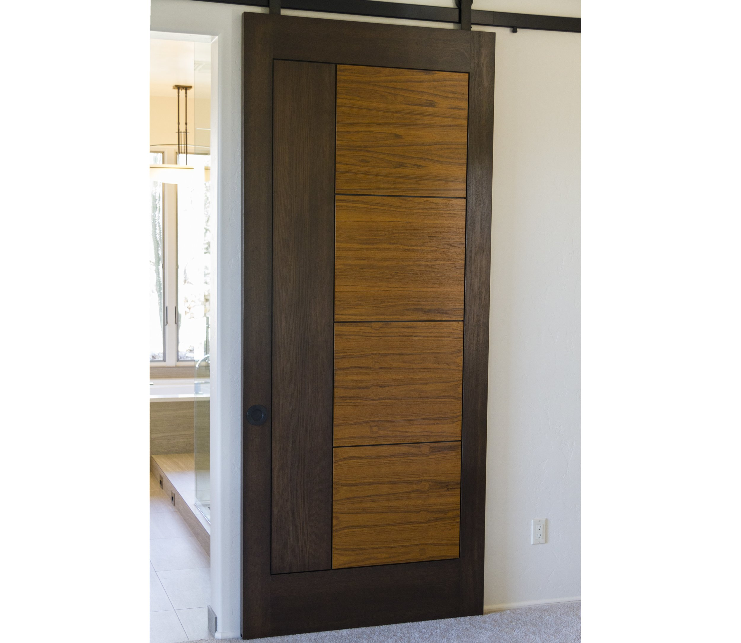 Barn Door - The homeowners wanted to keep a touch of whimsy and were easily sold on these unique sliding barn doors.A pair of custom wood sliding barn doors grace the far wall. The doors are constructed of rift-sawn white oak with teak panels. When closed, they hide the entry to the Master Bathroom and walk-in-closet.