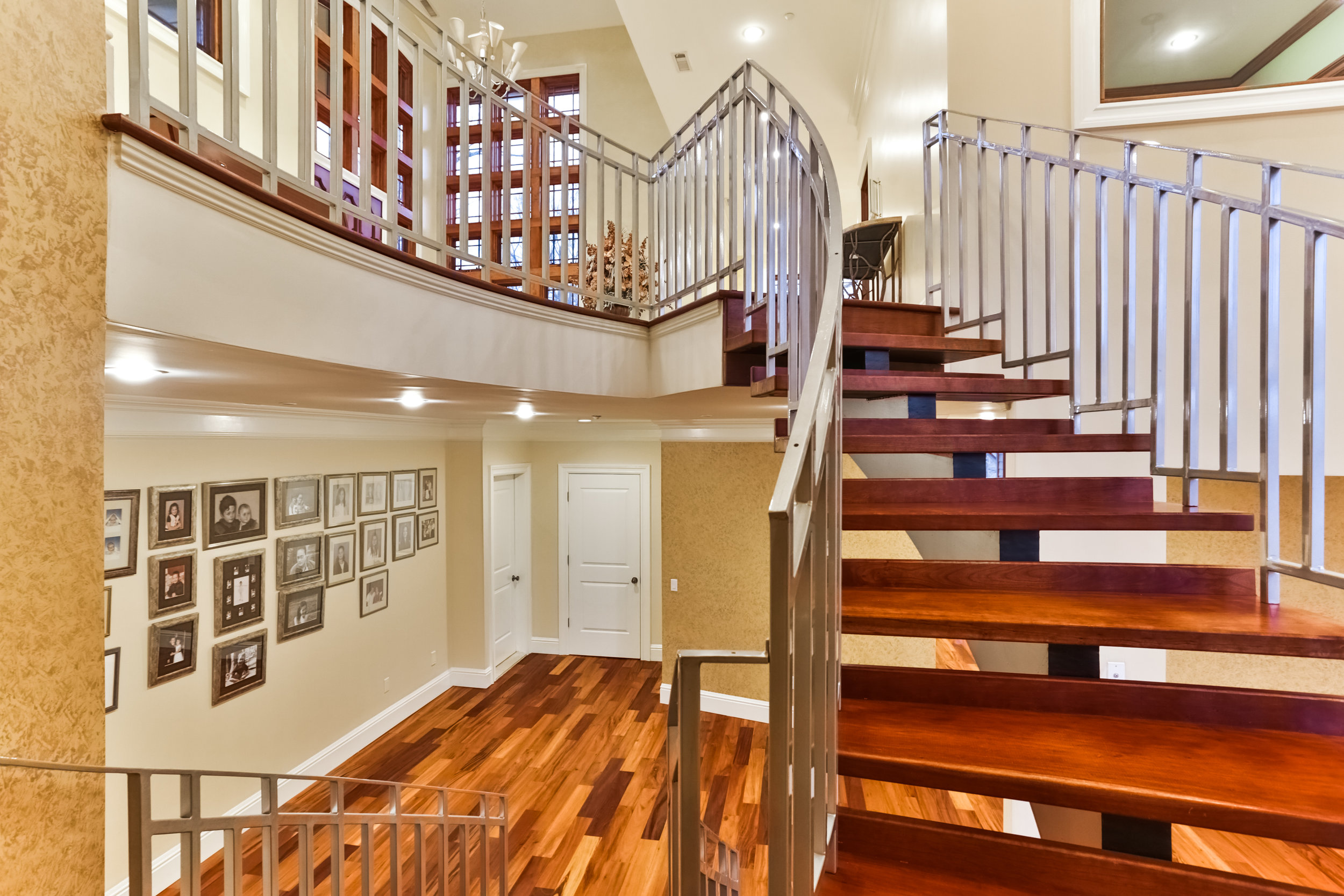 Handcrafted spiral stairs case leading from the upstairs foyer to the downstairs area