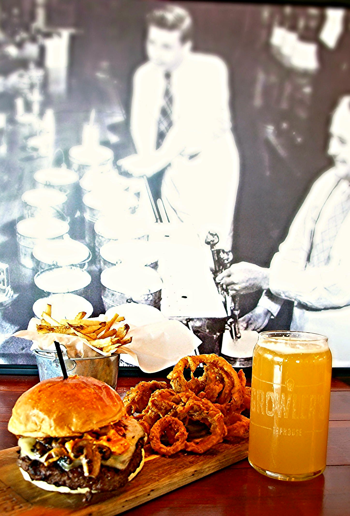 Growler's Meatwagon burger with onion rings (the best in Tucson), fries (also the best in Tucson), and a beer. Photo taken in front of a picture of bartenders after Prohibition serving beer in the original growlers.