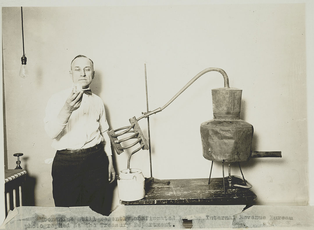 An Internal Revenue Service agent scrutinizes the contents of a moonshine still during the Prohibition era.