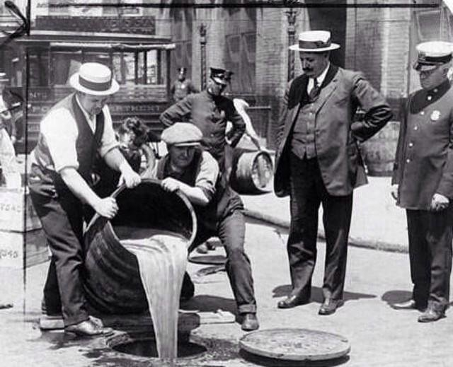 New York City Deputy Police Commissioner John A. Leach, right, watches agents pour liquor into sewer following a raid of a distillery