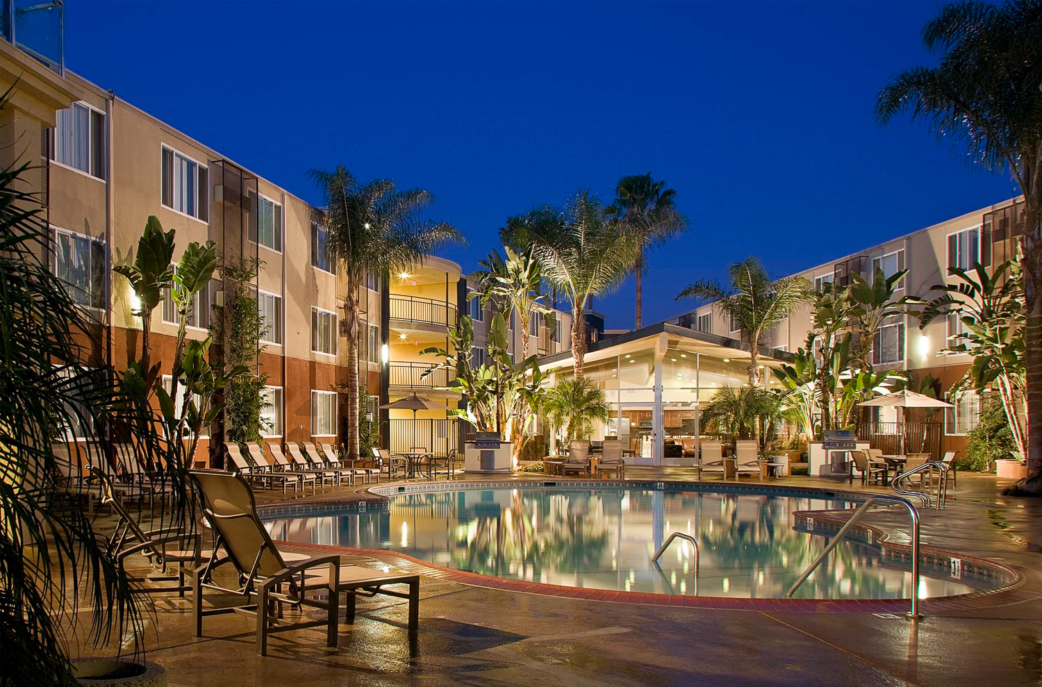 Dusk exterior with tungsten lighting. Photography of 1900 Riverside for Sares Regis Apartment Communities.