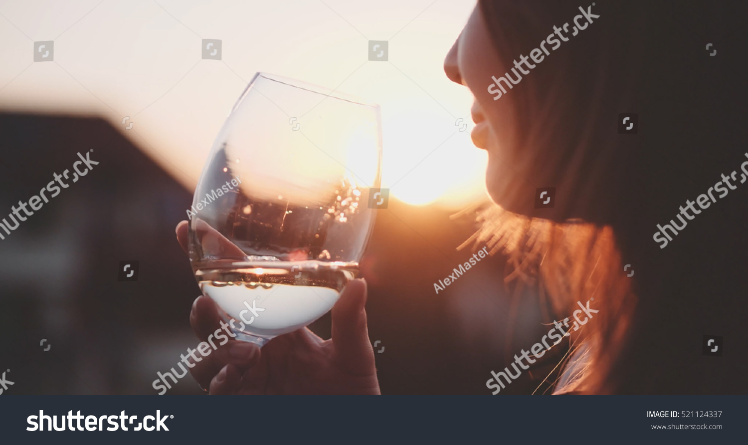 stock-photo-woman-drinking-cooled-white-wine-from-a-glass-at-the-balcony-during-sunset-beautiful-female-521124337.jpg