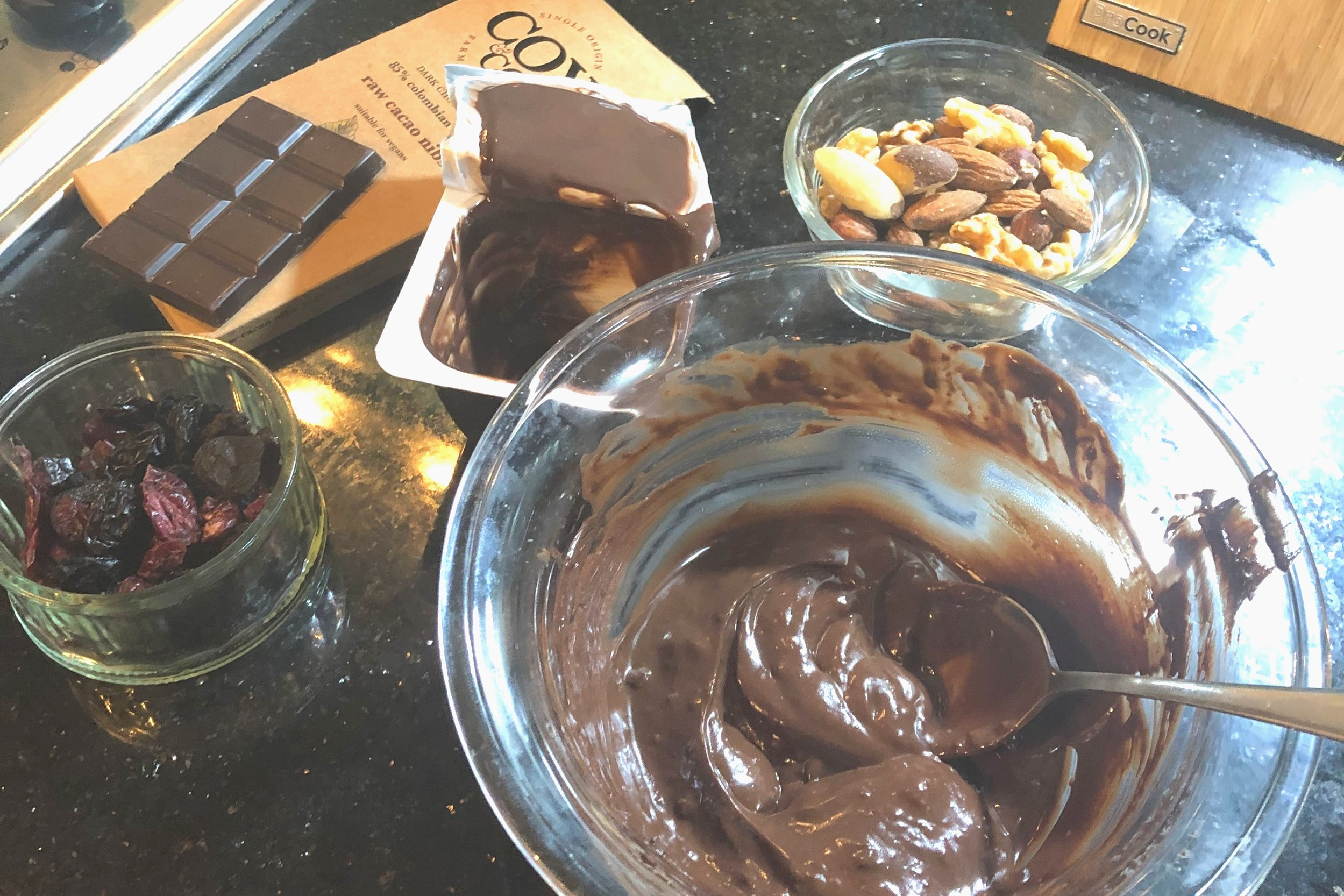 INGREDIENTS:  Cox&Co. 85% Cacao with Raw Cacao Nibs, 80g  Dark Chocolate Alpro Pot  Chopped up mixed nuts  Chopped up mixed dried berries  METHOD:  Melt one 80g bar of 85% Cacao with Cacao Nibs over boiling water  Once fully melted, still in the pan, mix in the dark chocolate Alpro pot  Teaspoon small puddles on to baking paper  Sprinkle your chopped nuts and fruit on top  Put in the freezer for 1hr to set  Take out of the freezer 15mins before serving and ENJOY!