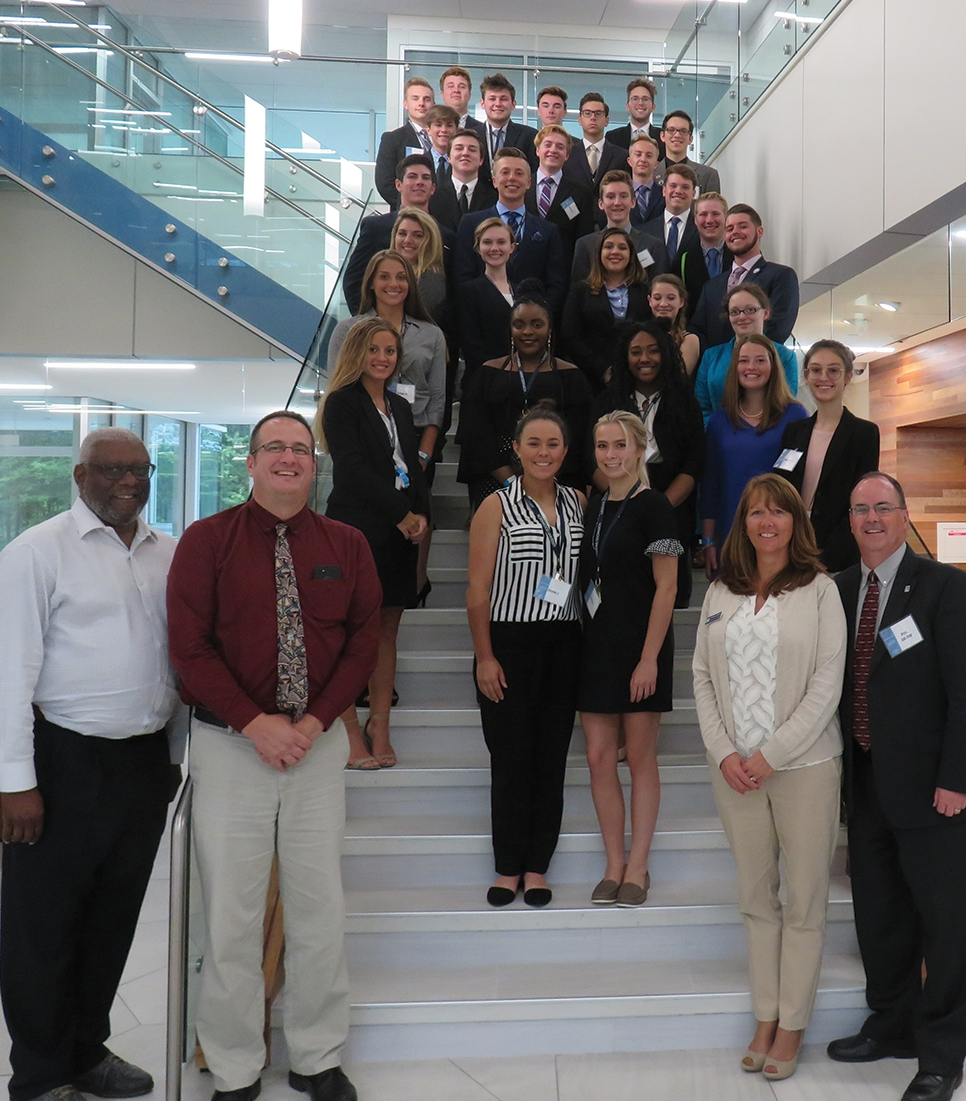 The members of LAB Camp's 2018 class pose with their instructors inside the DeVos Graduate School building.