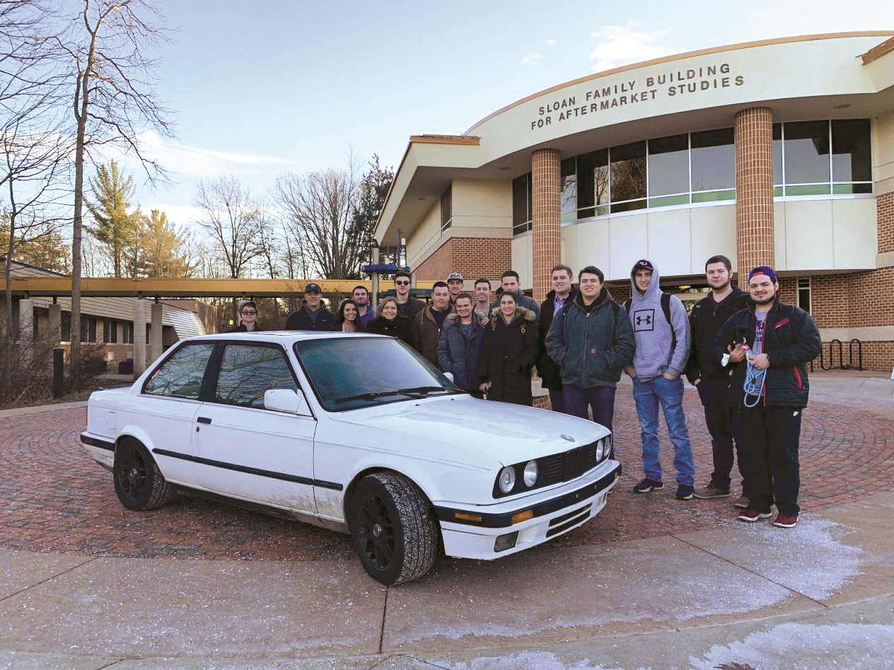 Members of the fall 2018 Project 100 winner, the Aftermarket Club, gathered around the 1989 BMW E30 they bought.