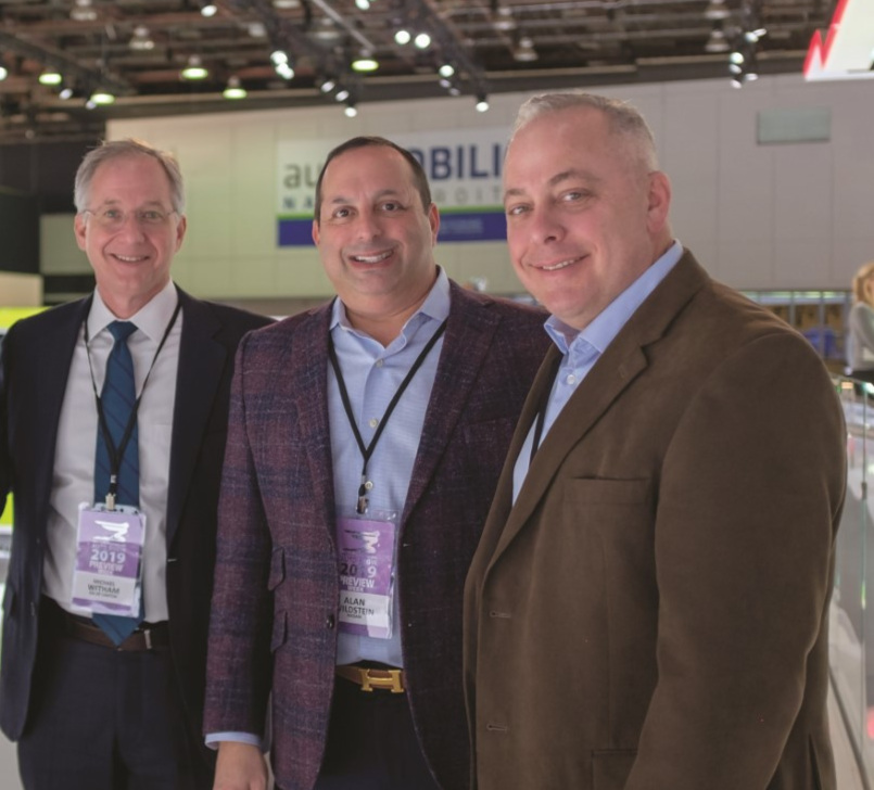 Business partners, from left, Michael Witham ('89), Art White ('90), and Alan Jay Wildstein ('89) posed for a photo together at the North American International Auto Show in Detroit.