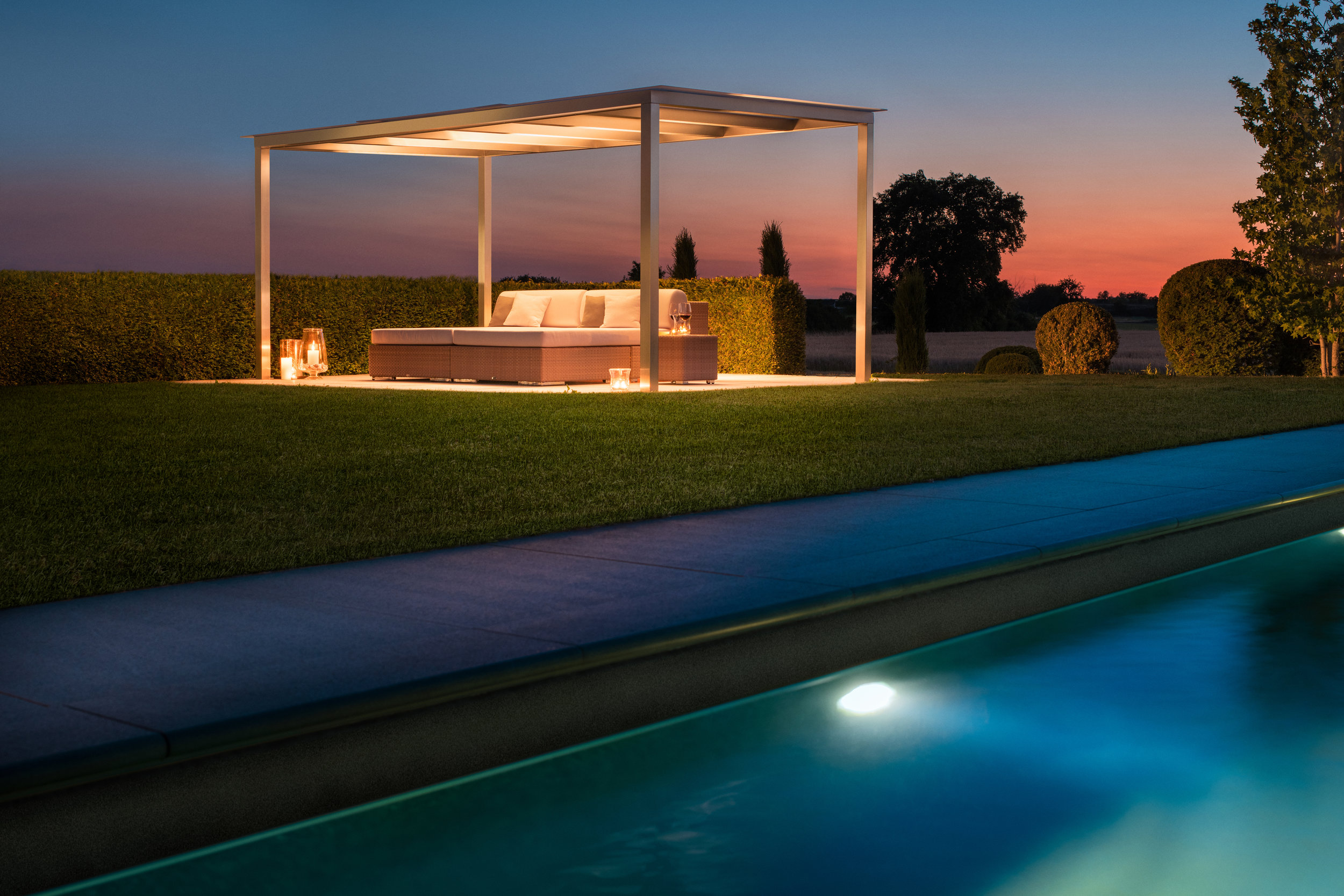 rewalux Pergola in stimmungsvoller Abendstimmung am Pool