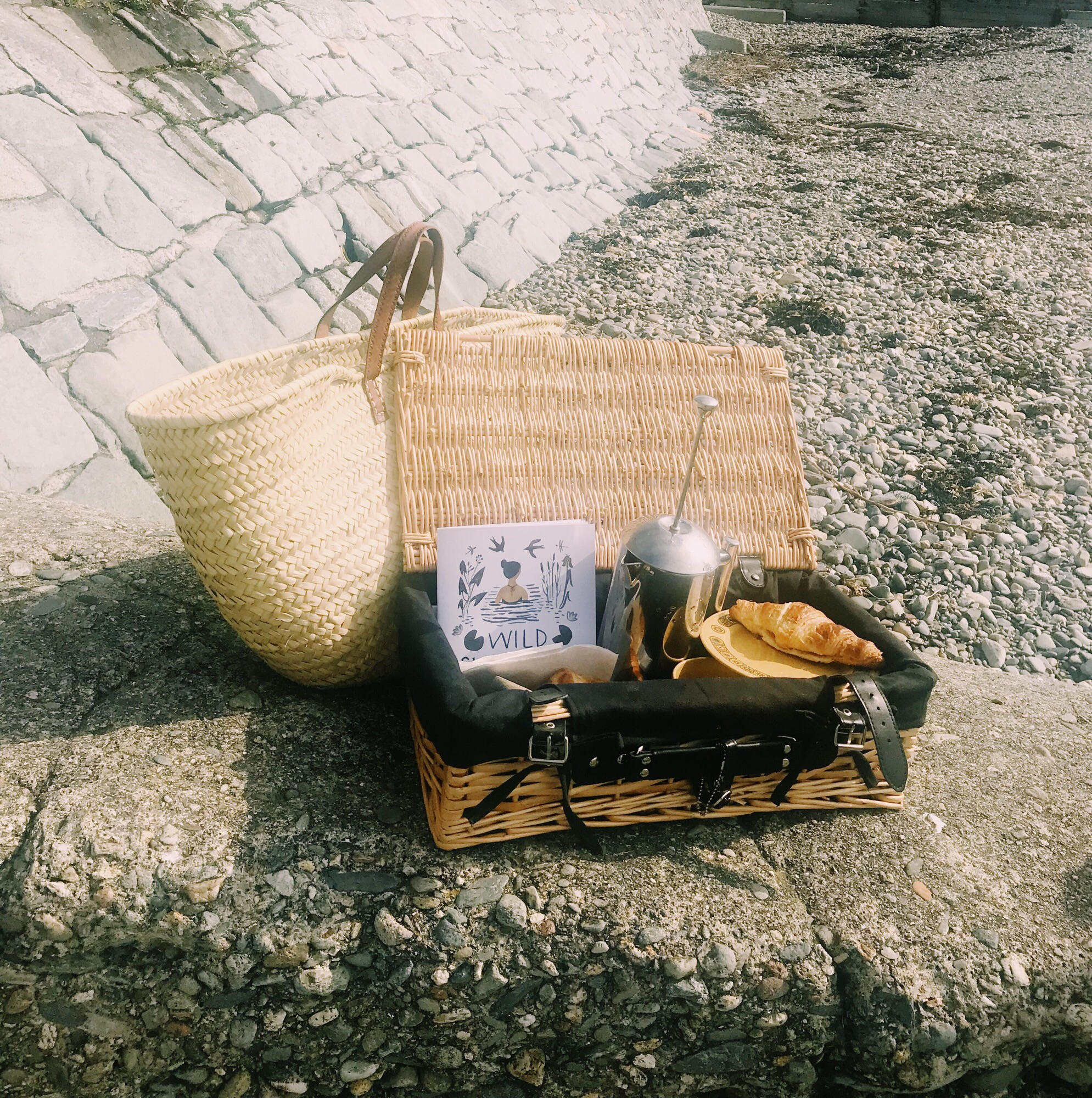 Beach picnic essentials - coffee, carbs and the  wild swimming book