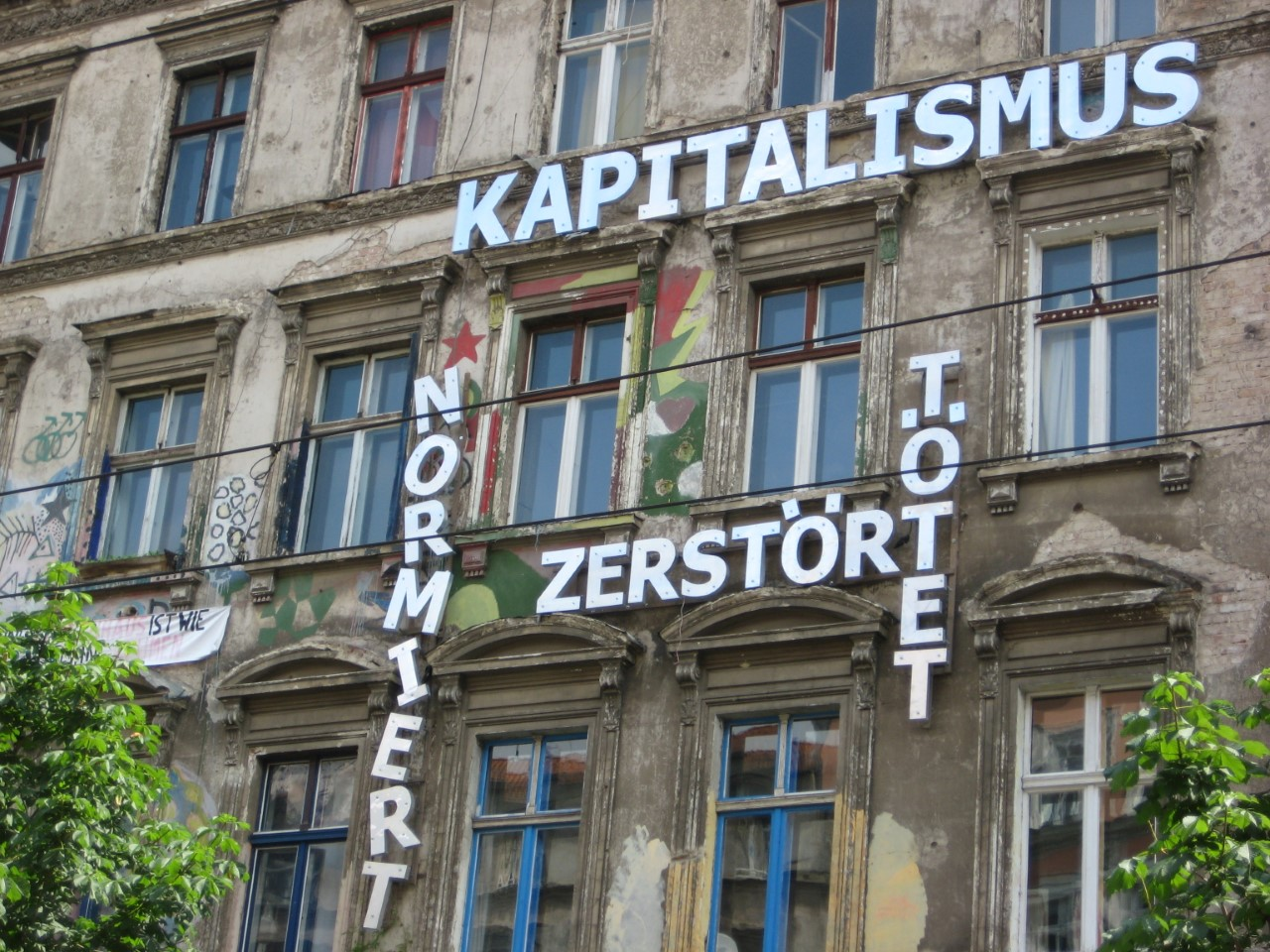 """A message on the facade of Kastanienallee 86 reads """"Capitalism normalizes, destroys, kills"""". The building contains two Hausprojekte, or """"living projects"""" that proliferated the new city center of reunified Berlin: the Tuntenhaus, or """"Queer House"""", takes up the back wing of the building, and the KA 86 Hausprojekt faces the street. 2007. Courtesy of Daniela Sandler."""