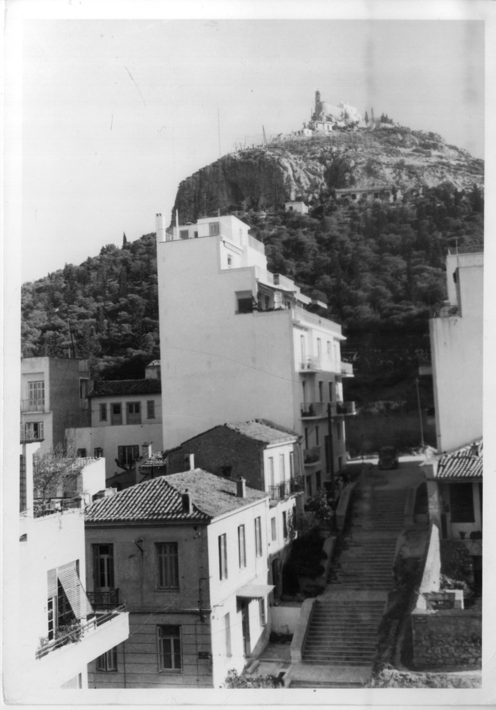 A view of Lycabettus Hill, ca 1950. Below, a typical street in the upper-middle class area of Kolonaki with neoclassical and early nineteenth-century domestic buildings, just starting to be developed with new polykatoikía . © Benaki Museum, Costas.