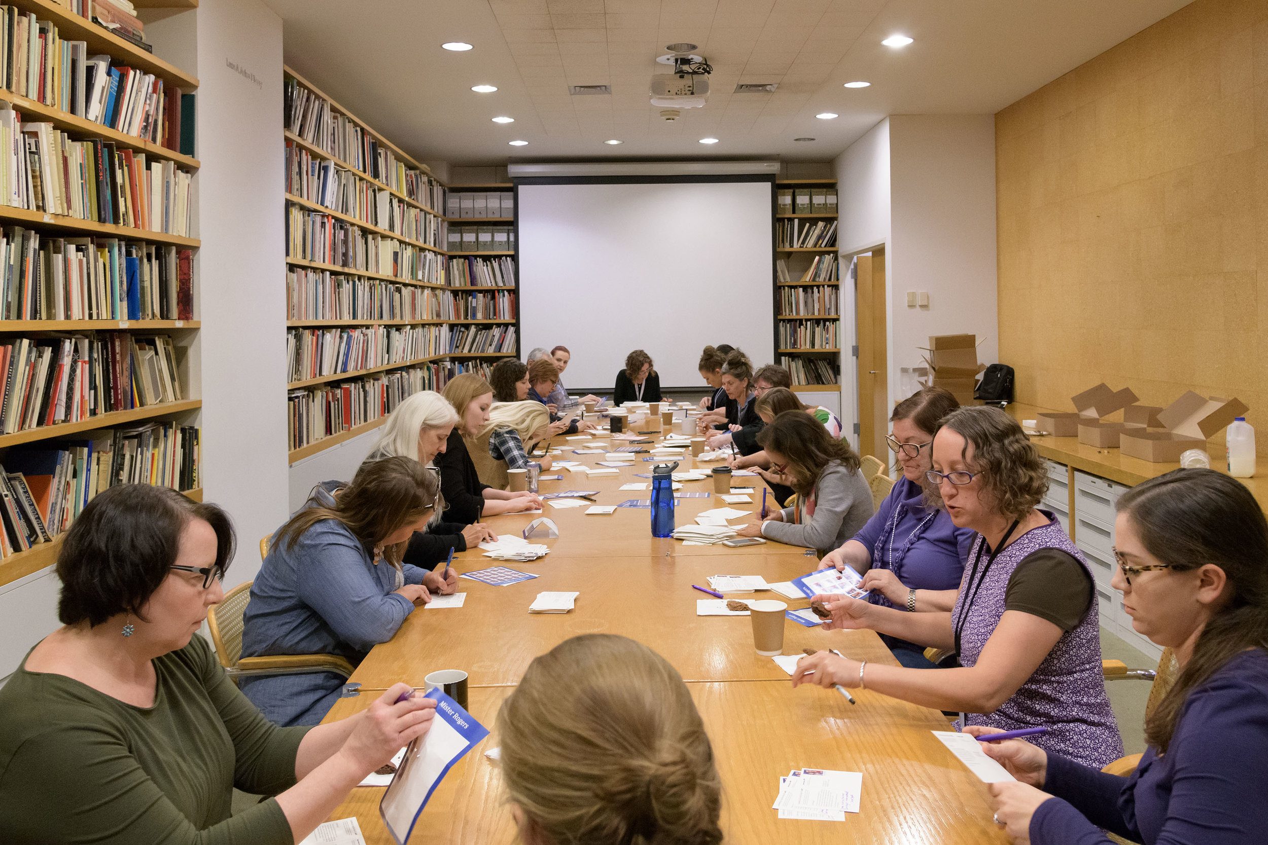 Carnegie Museum of Art staff writing 2,018 postcards inviting households across Pittsburgh to the 57th  Carnegie International . © Carnegie Museum of Art, Pittsburgh. Photo: Bryan Conley.