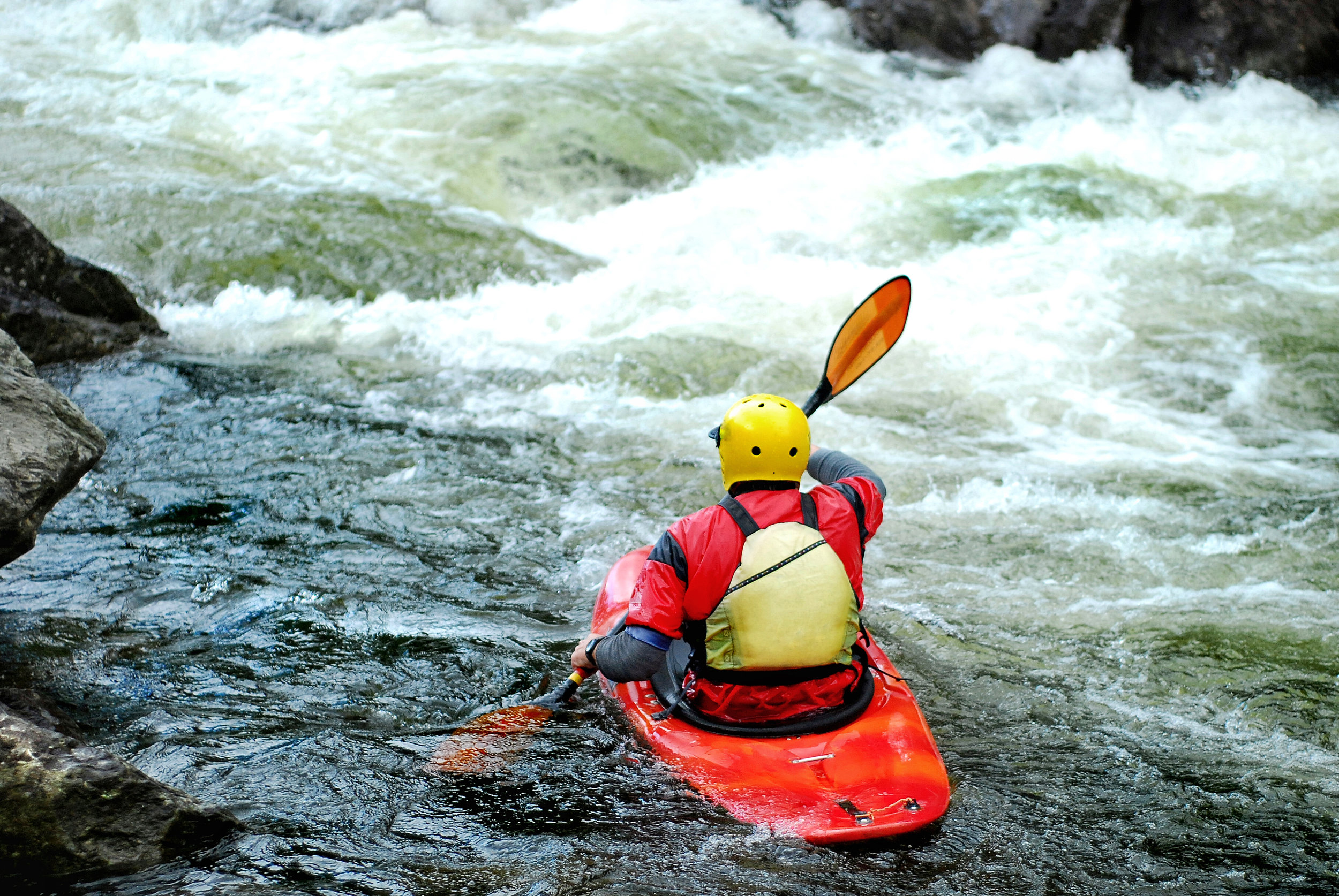 Back view of a red kayaker riding down some whitewater rapids.