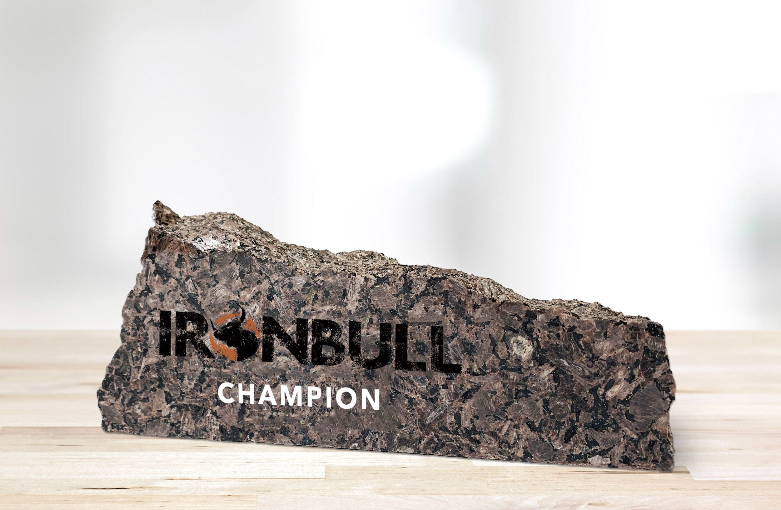 """The IRONBULL™ Ring Trophy, a chiseled piece of red granite displaying the IRONBULL™ logo and the word """"Champion,"""" sits on a wooden table."""