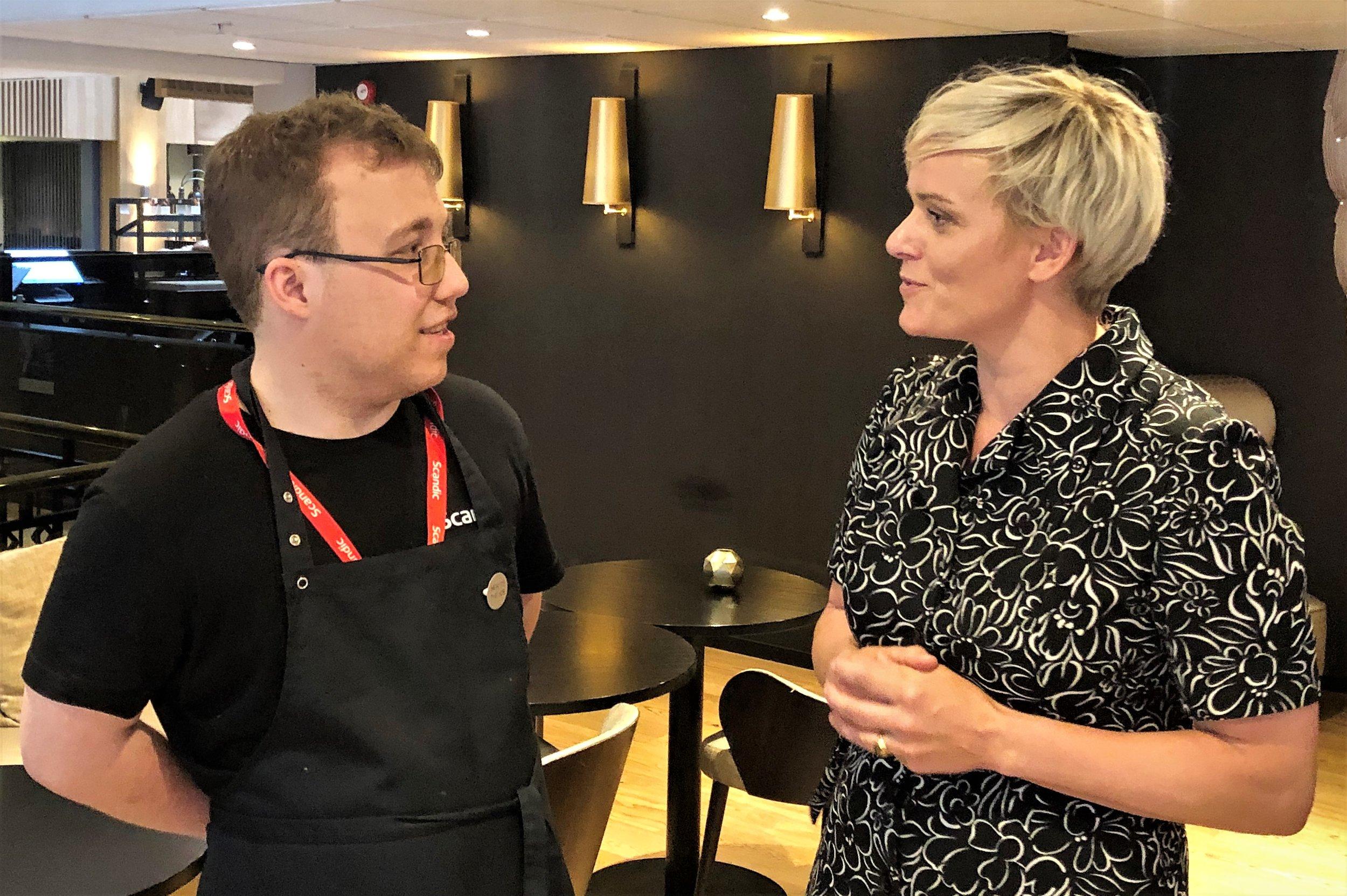 Fredrik Engebrektsen forteller stortingsrepresentant Margret Hagerup (H) om hvilke arbeidsoppgaver han utfører, hvordan det var å stå utenfor arbeidslivet og hvor mye det har betydd for ham å få denne muligheten av Scandic.