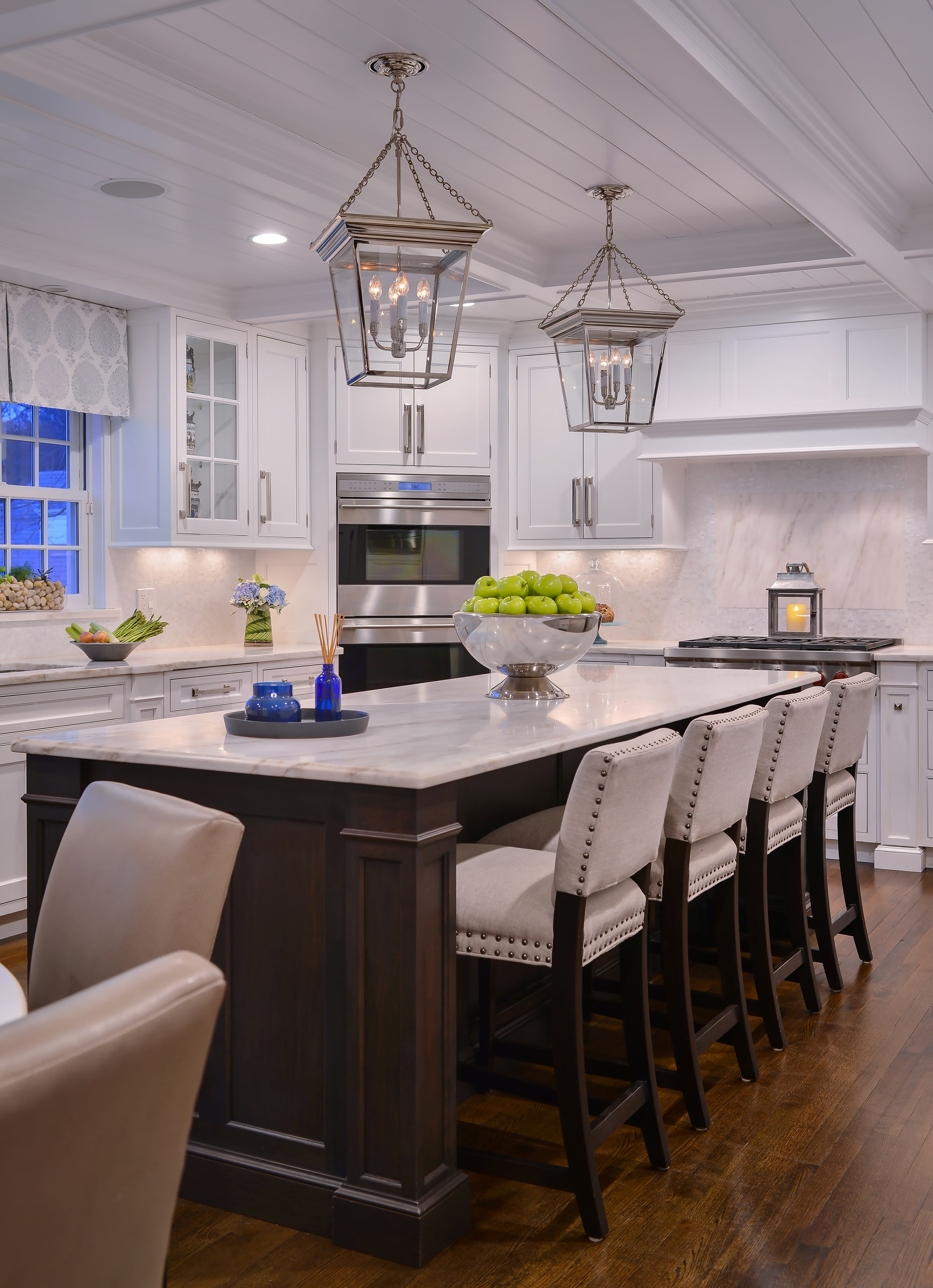Transitional style kitchen with kitchen island and four counter stools