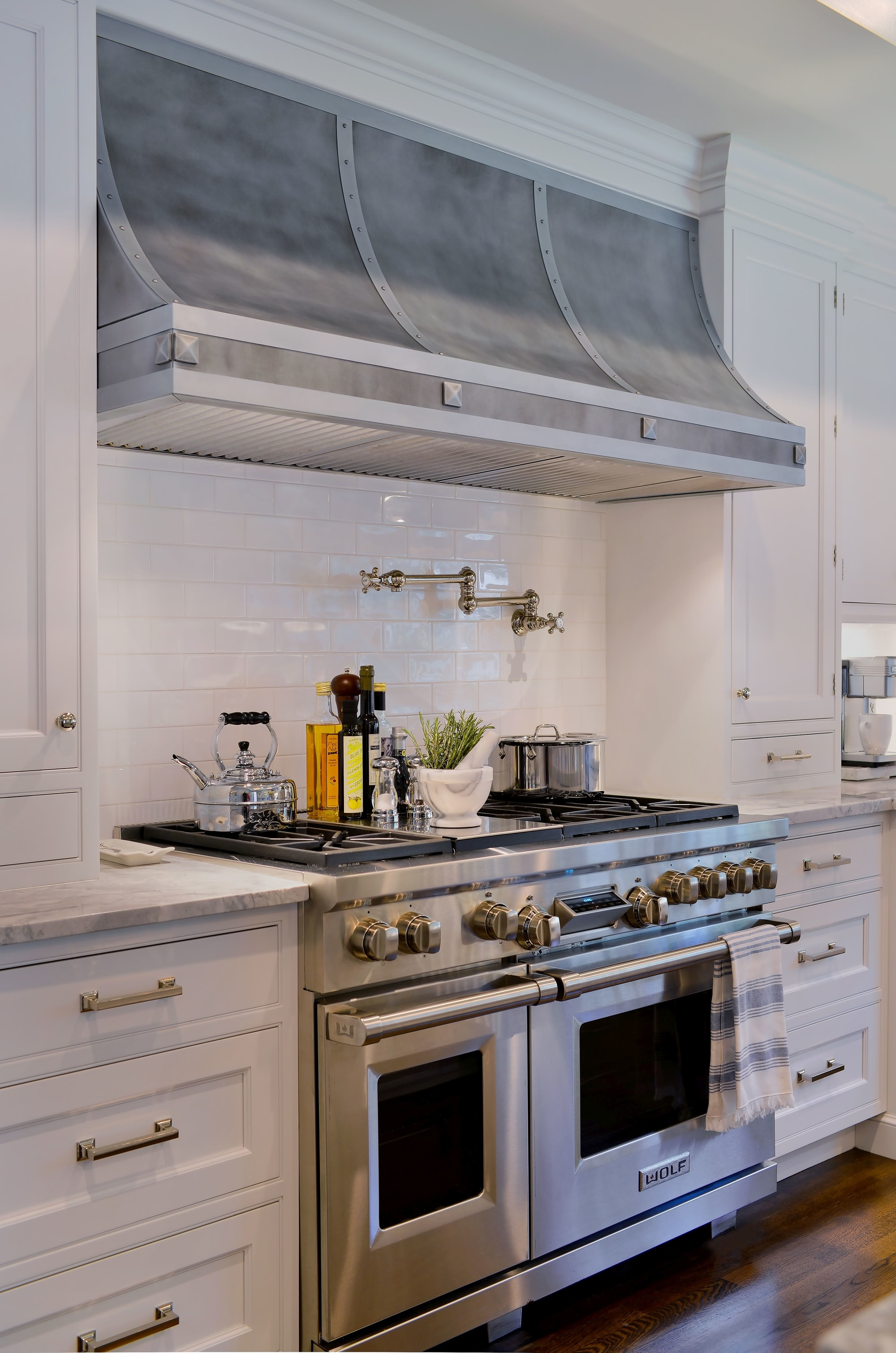 Transitional style kitchen with stainless range hood and range oven