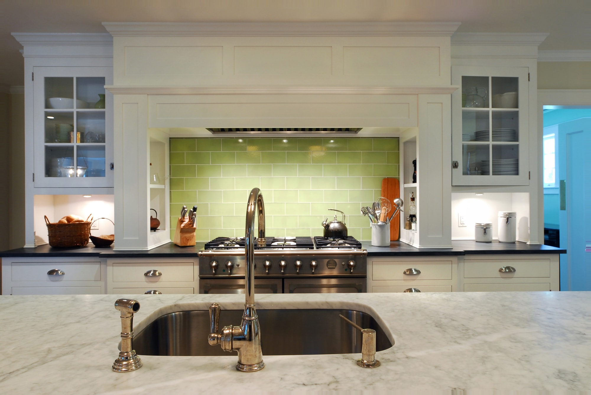 Transitional style kitchen with single hand faucet and marble countertop