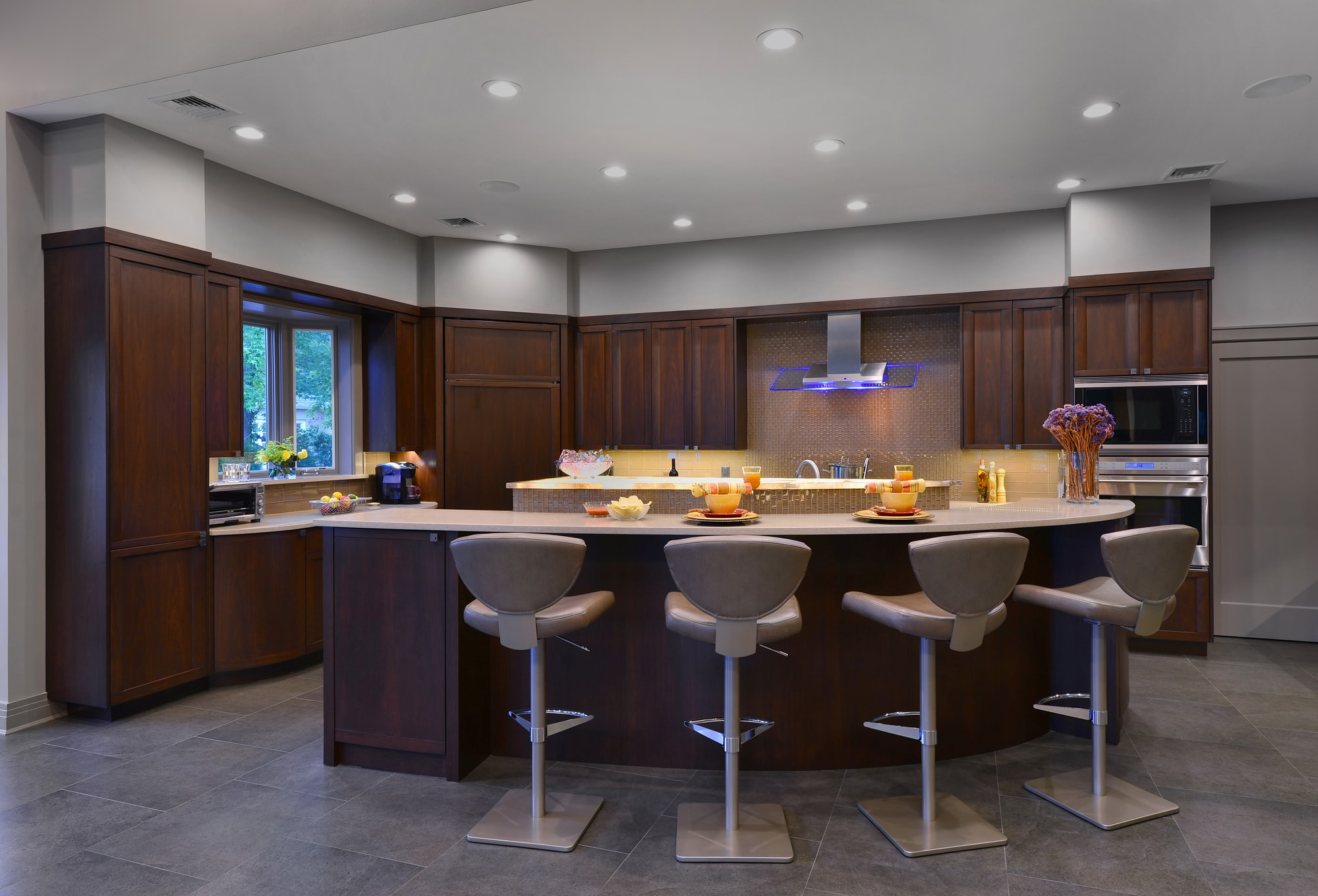 Transitional style kitchen with oval cut kitchen island