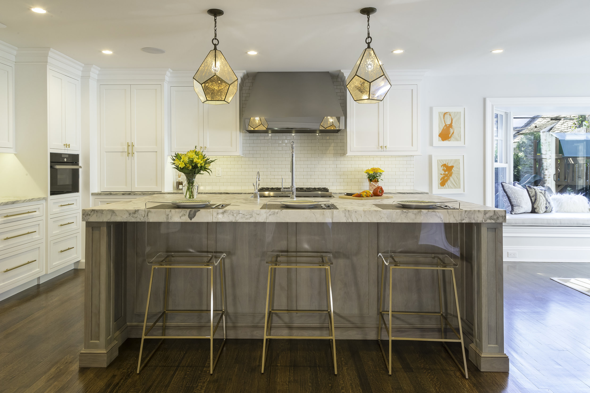 Transitional style kitchen with long white marble kitchen island