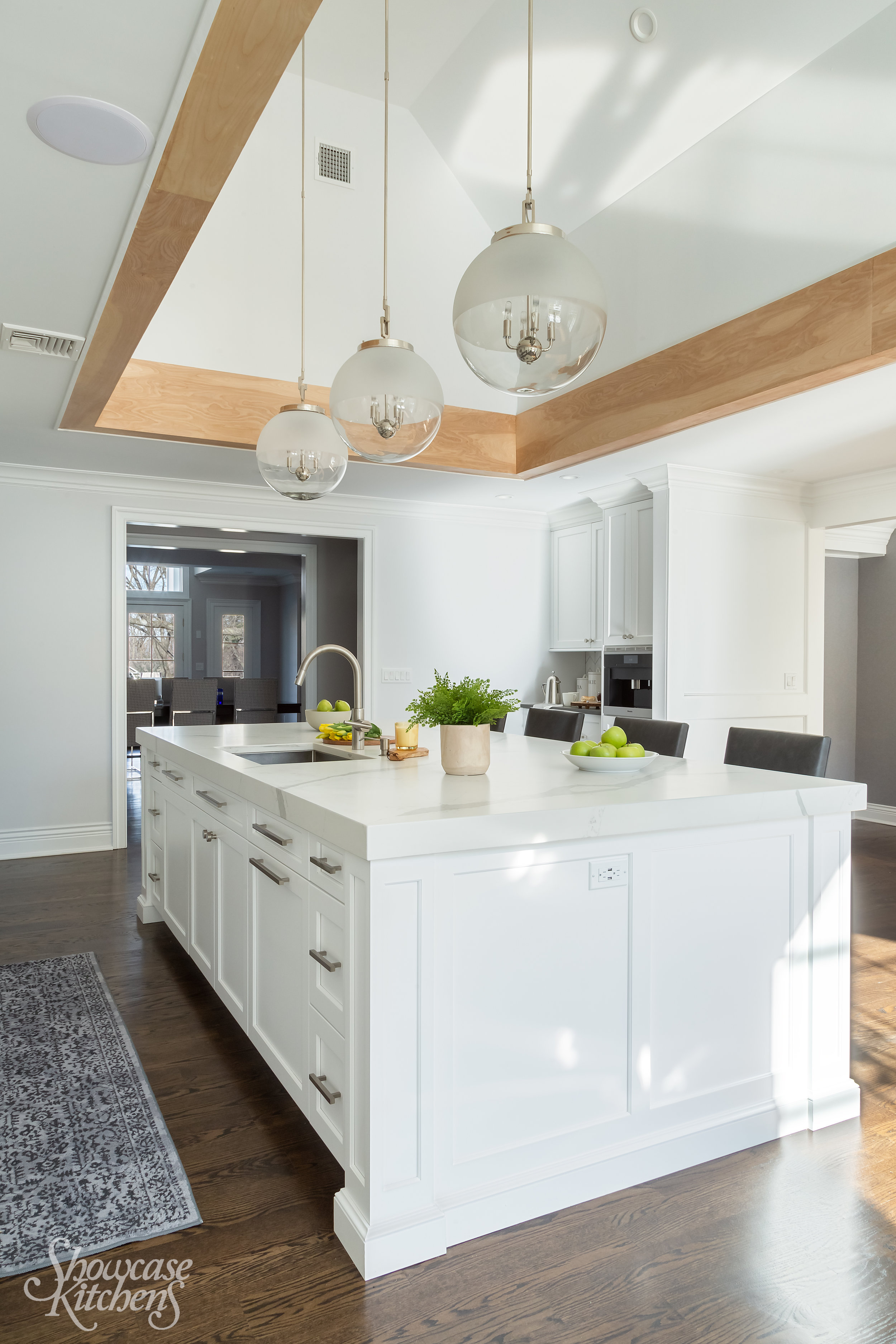 Transitional style kitchen with flying oak beam and large center island