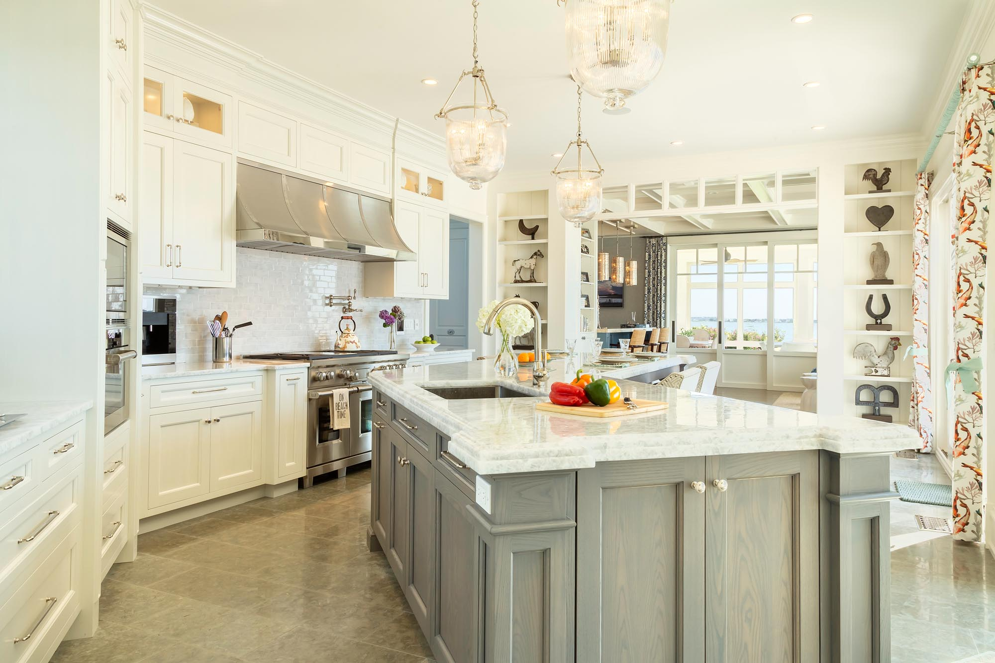 Transitional white kitchen with detailed millwork to hold client's collection