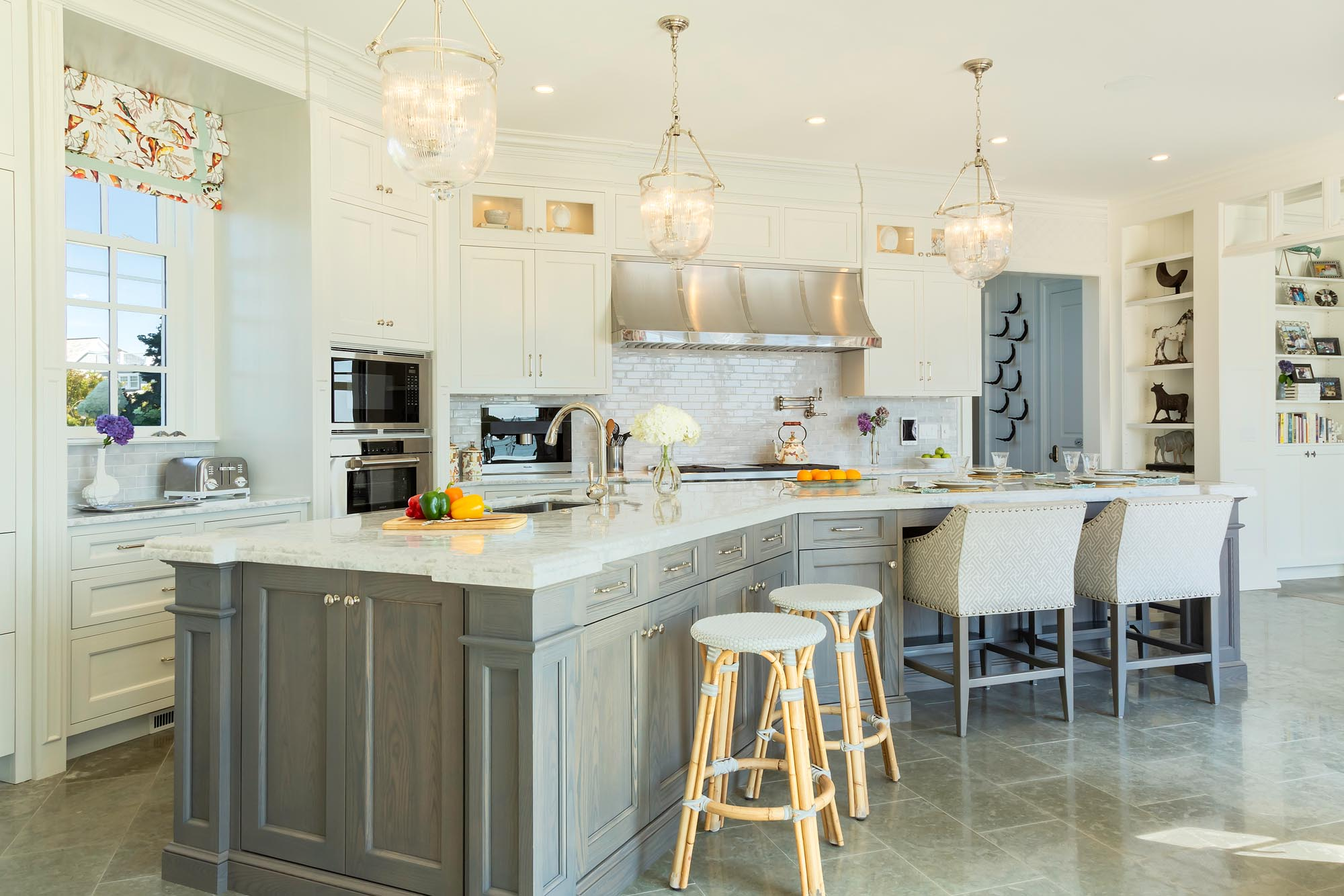 Transitional kitchen with V-shaped center island and white perimeter cabinetry