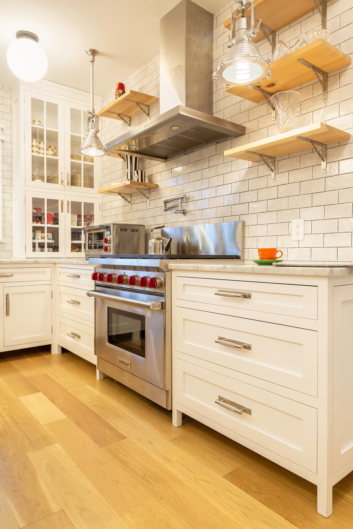 Transitional white kitchen with high end oven and stainless steel hood