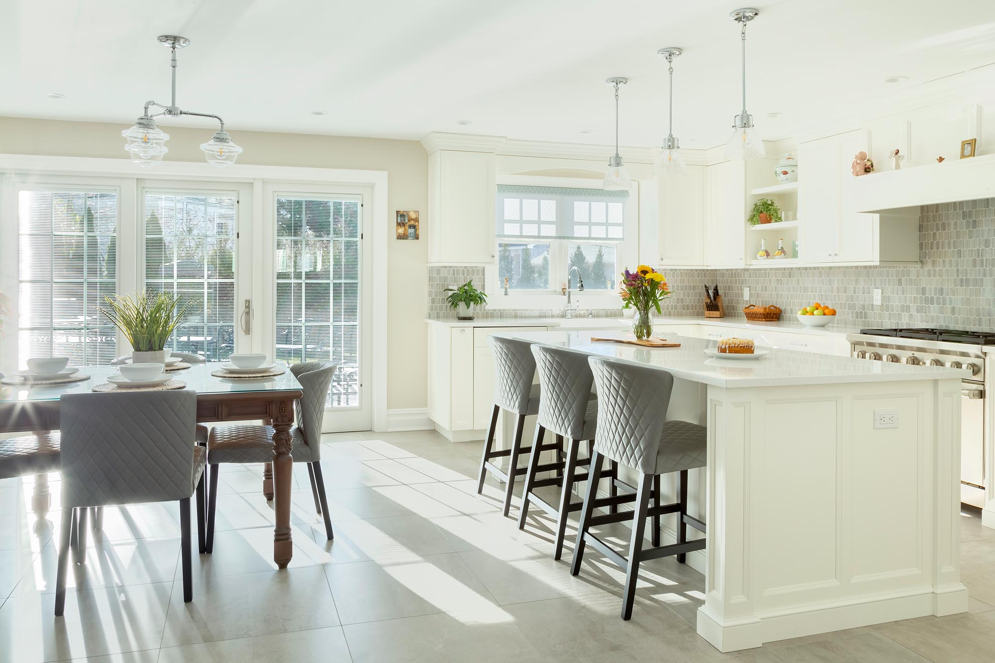 Transitional white kitchen with center island and wooden dining room table