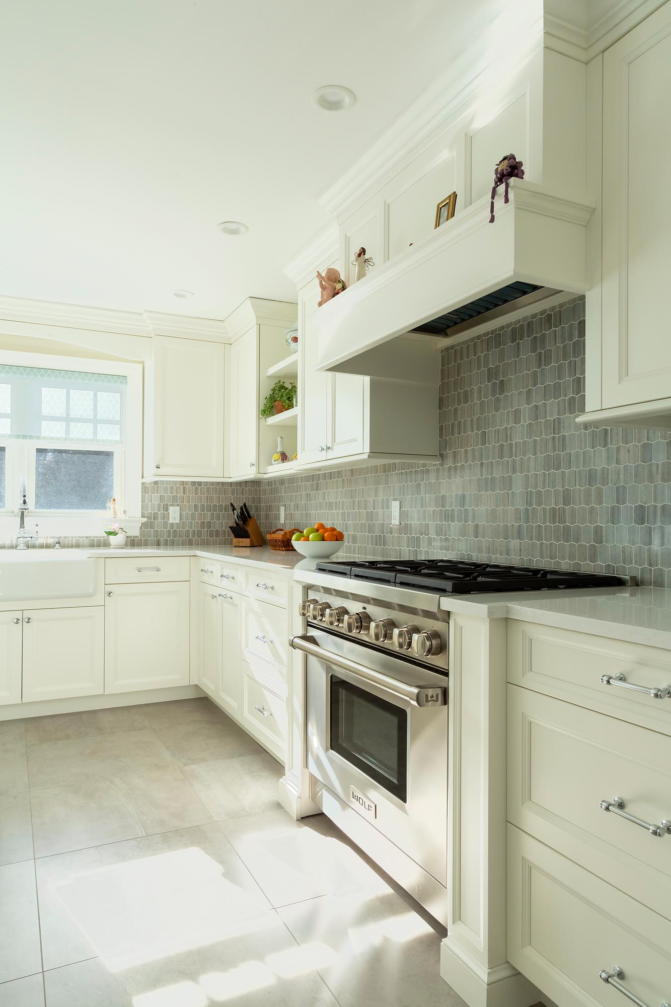 Transitional white kitchen with mantle hood and Wolf range