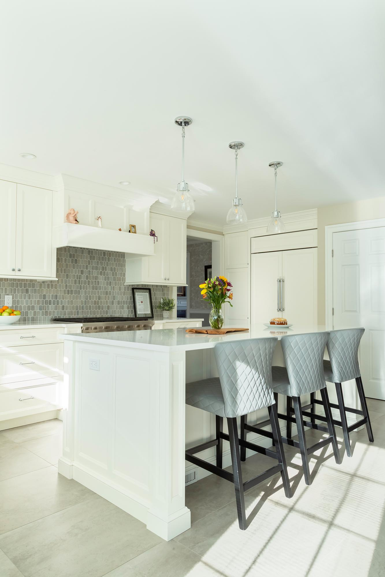 Transitional white kitchen with white center island and stools