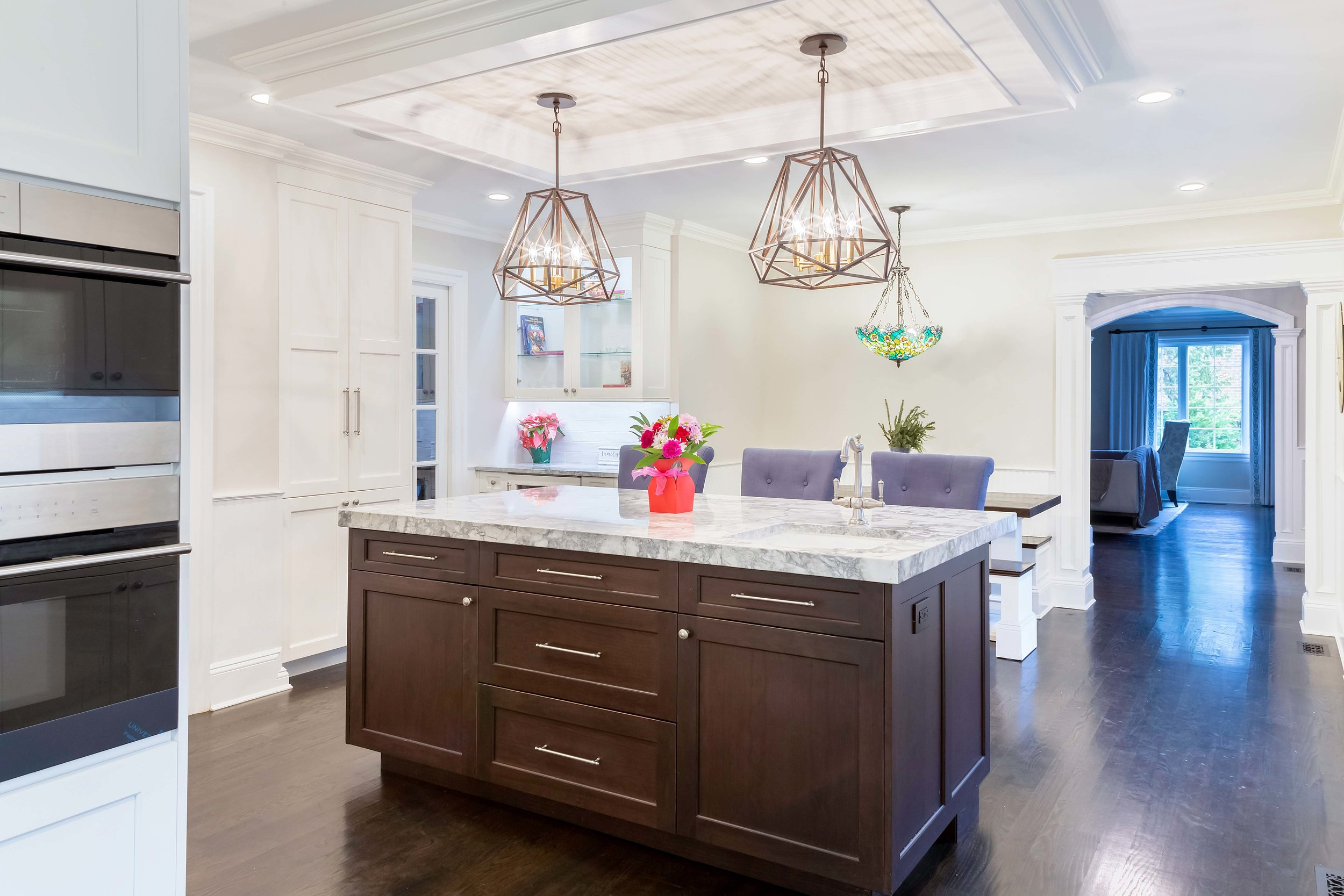 Transitional kitchen with cherry center island with contemporary light fixtures and tray ceiling