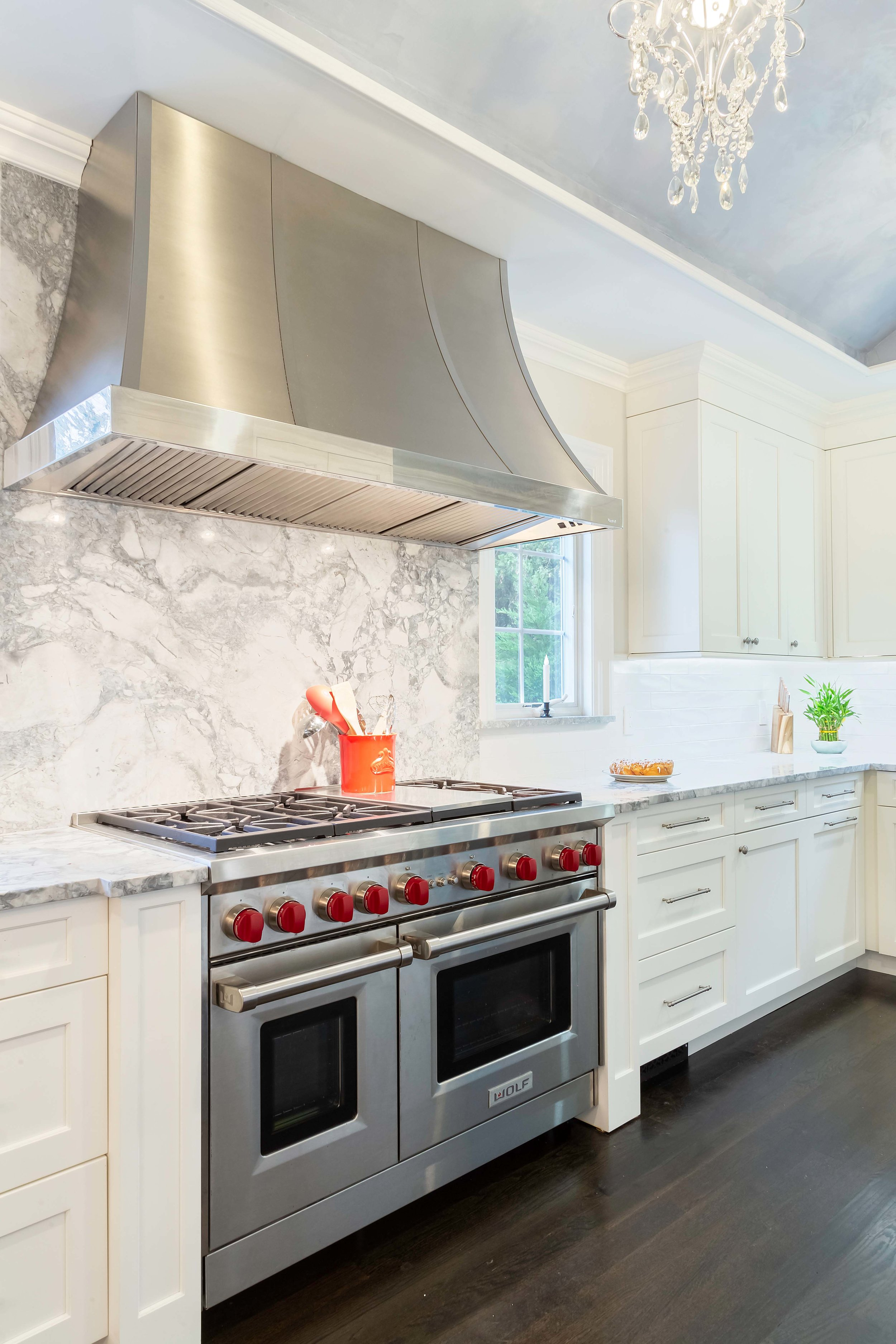 Bright kitchen with Wolf range and hood and dark stained floors
