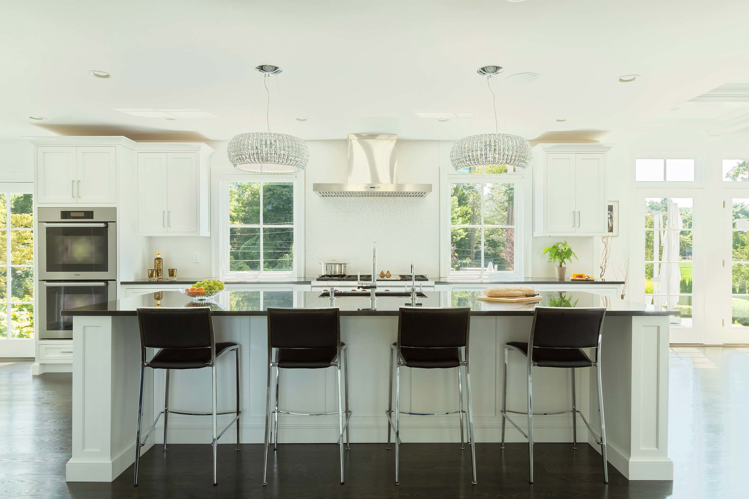 Transitional white kitchen with black granite countertop