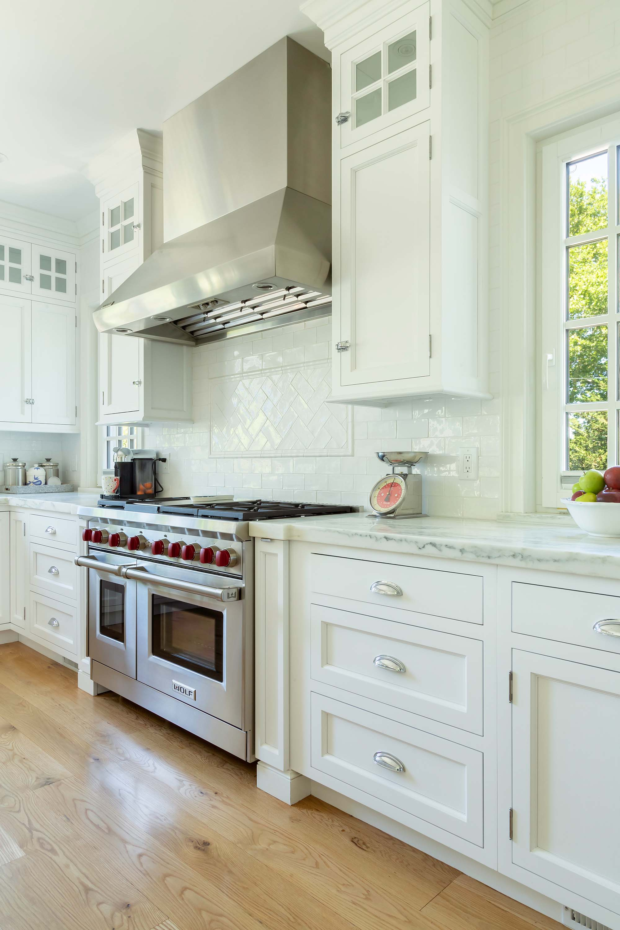 Transitional white kitchen with Wolf oven and range hood