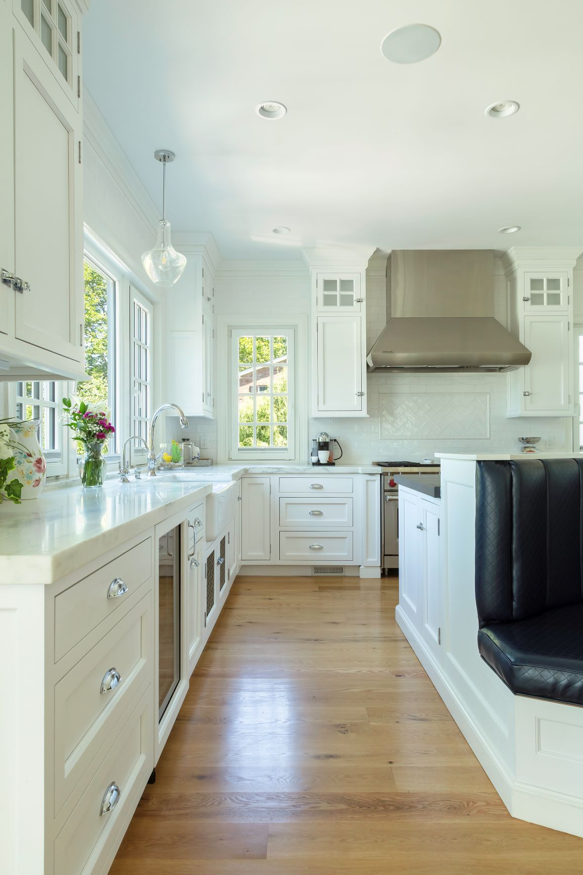 Transitional kitchen with oak flooring and stove pipe range hood
