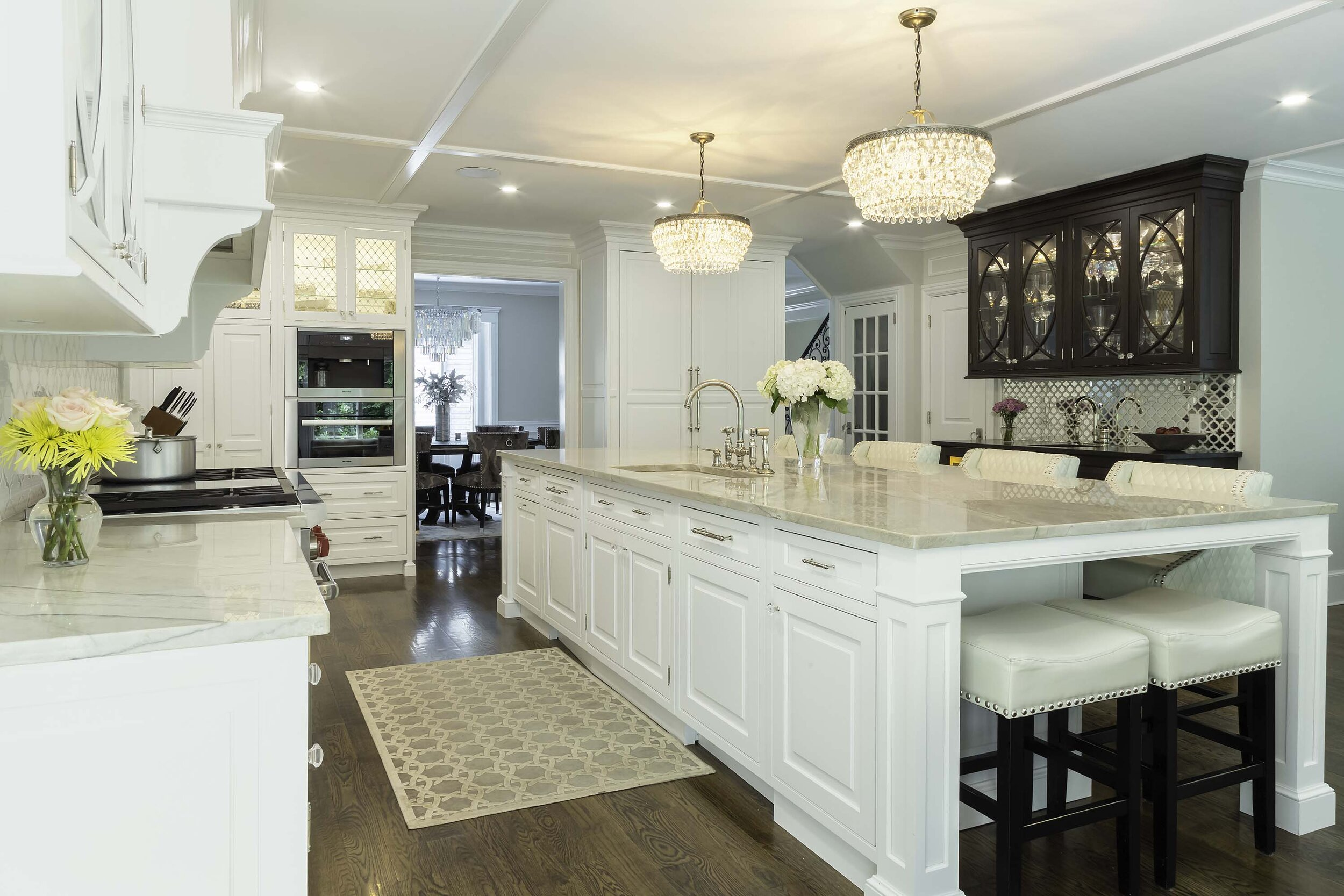 Traditional white kitchen on Long Island with granite countertop and nail head stools