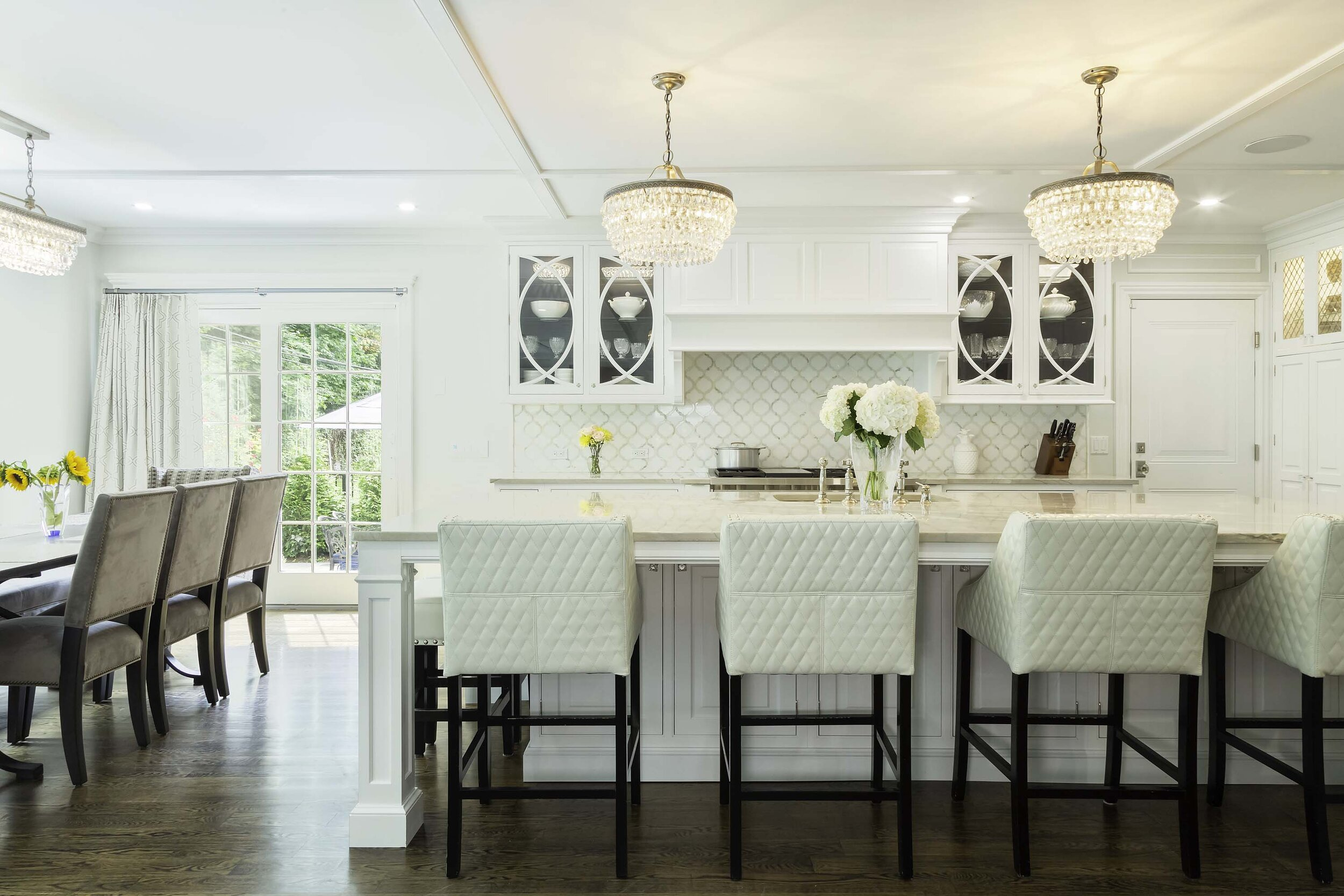 Traditional white kitchen with curved mullion doors and cross-patterned details