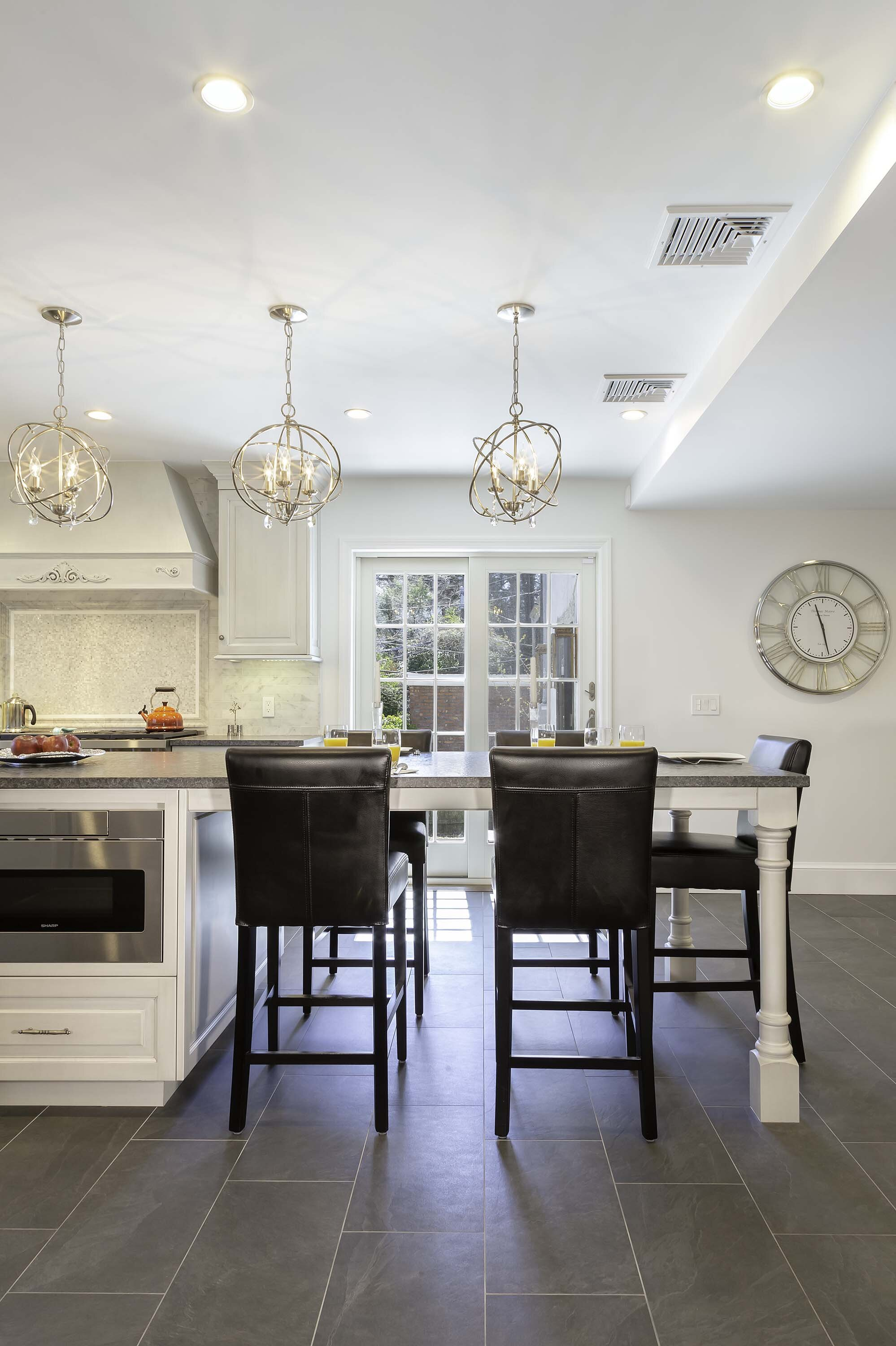 Long Island kitchen with leather counter stools and modern pendant lighting