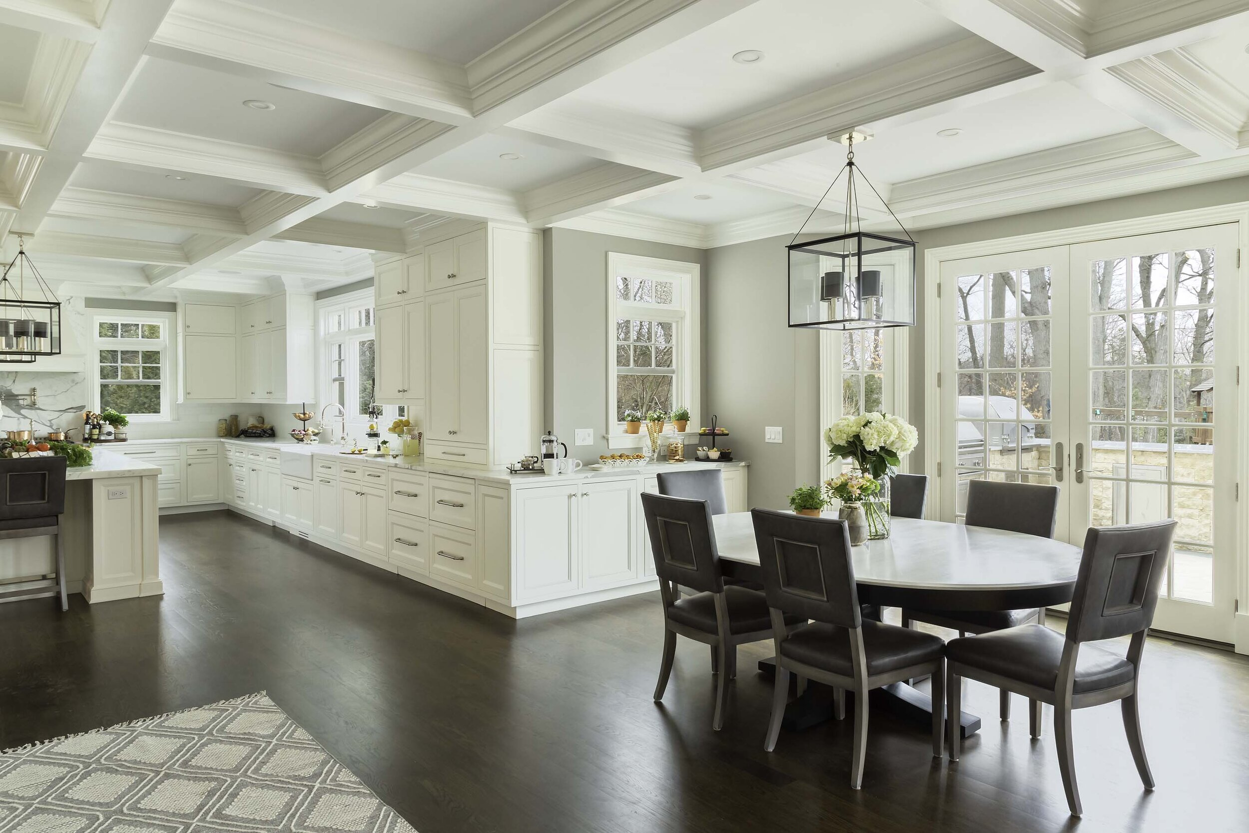 Transitional white kitchen with breakfast area overlooking patio