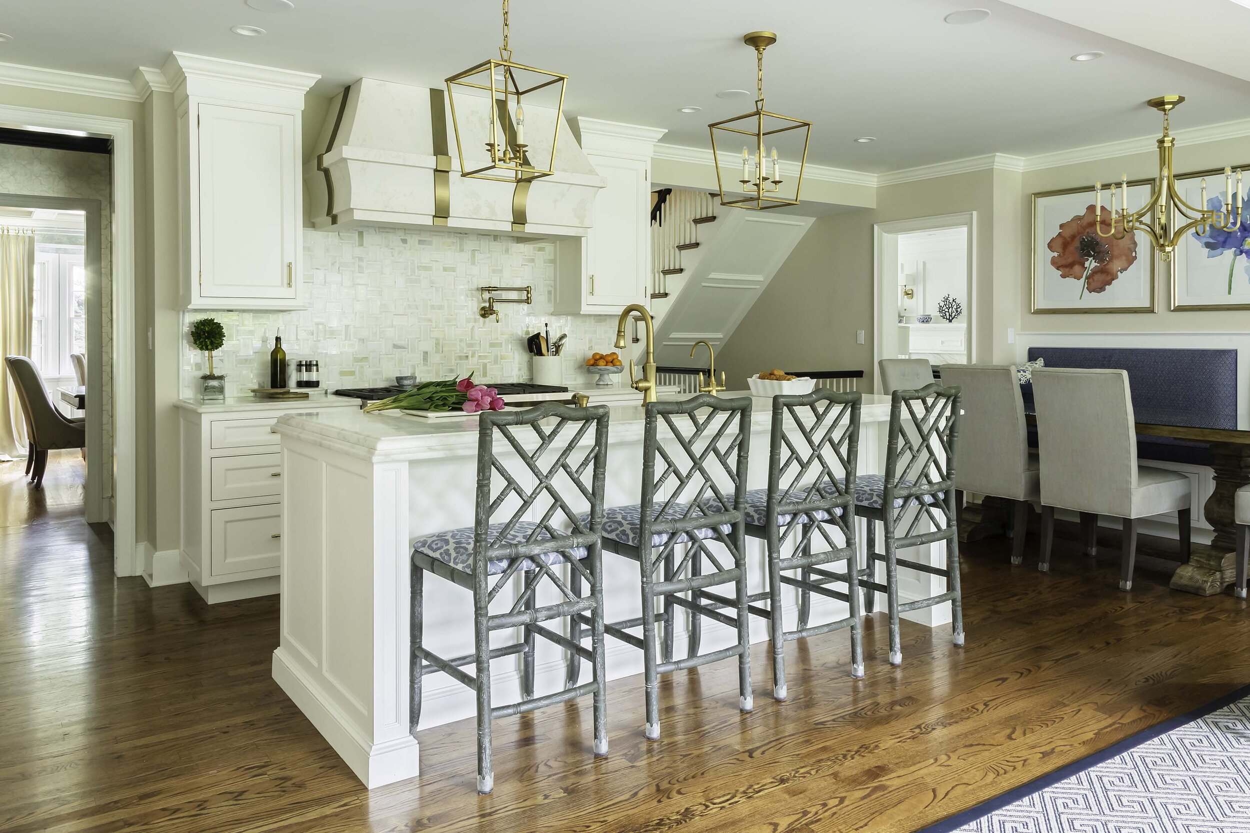 transitional white kitchen with brass accents opens to the family dining area